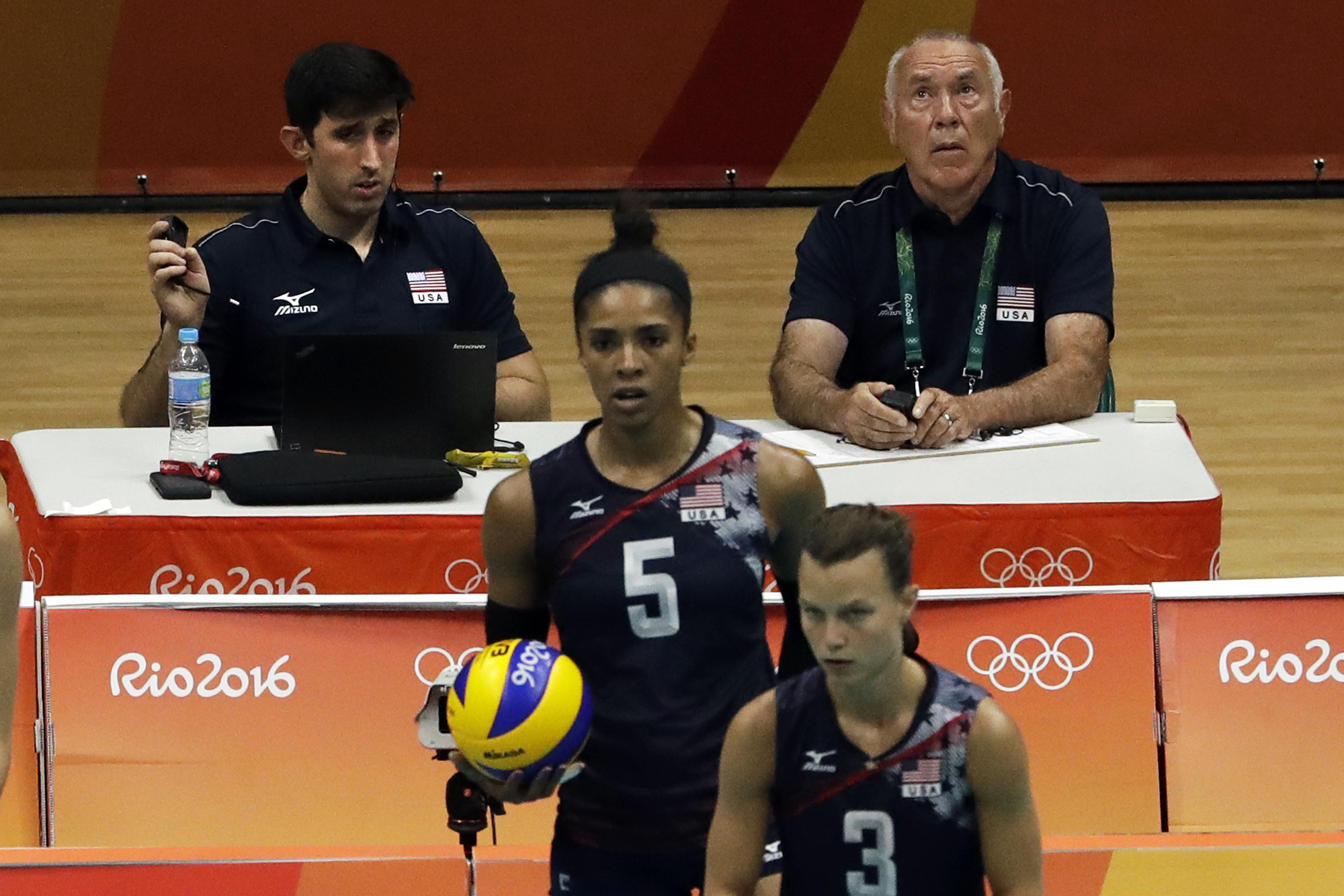 In this Sunday, Aug. 14, 2016 photo Joe Trinsey, left, technical coordinator for the United States women's volleyball team and coach consultant Marv Dunphy, right, view warmups ahead of a women's preliminary volleyball match at the 2016 Summer Olympics in