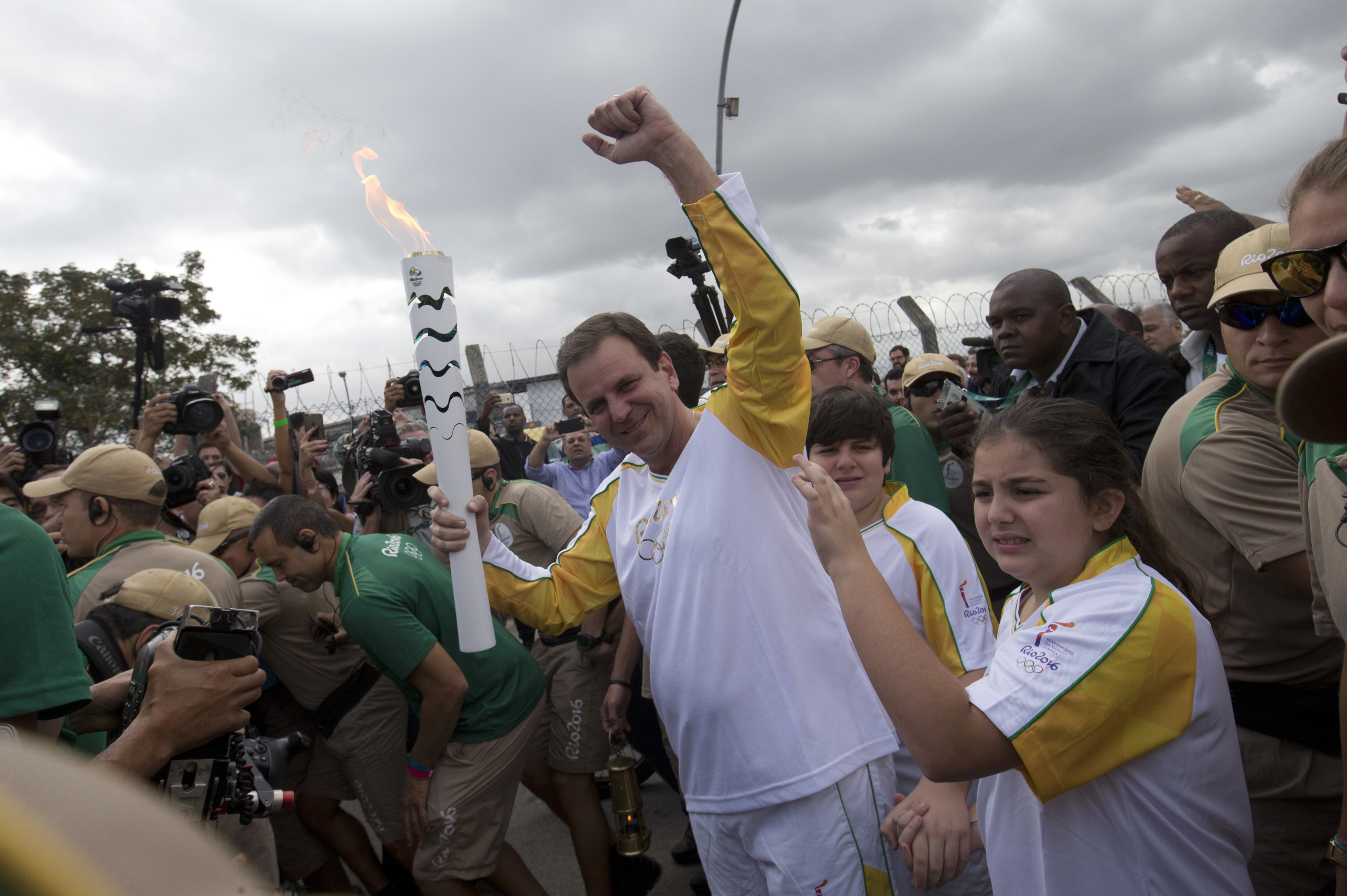 FILE - In this Aug. 3, 2016 file photo, Rio de Janeiro's Eduardo Paes, center, holds the Olympic torch on its way for the opening ceremony of Rio's 2016 Summer Olympics, in Rio de Janeiro, Brazil. Paes has been the face of the Rio Olympics, but he's been