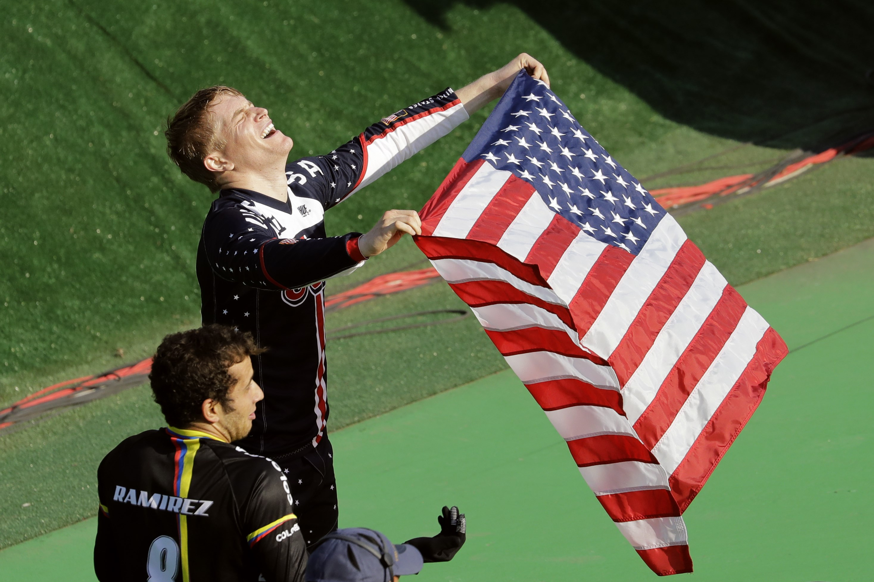 Connor Fields of the United States, top, celebrates after winning gold in the men's BMX cycling final next to third placed Carlos Ramirez Yepes of Colombia, bottom, during the 2016 Summer Olympics in Rio de Janeiro, Brazil, Friday, Aug. 19, 2016. (AP Phot