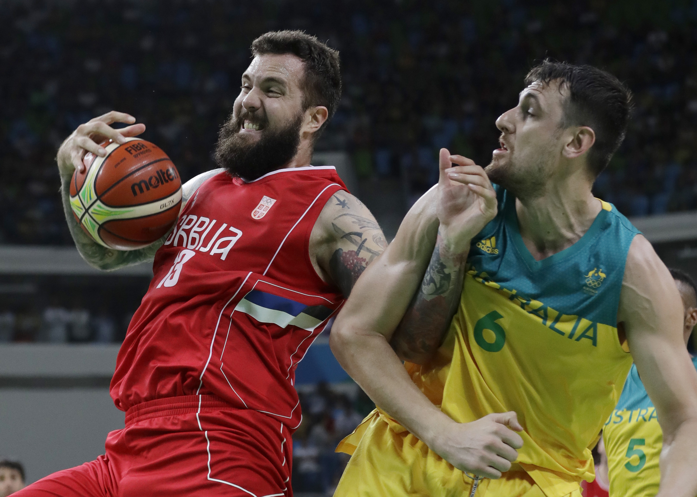 Serbia's Miroslav Raduljica (13) tries to work the ball around Australia's Andrew Bogut (6) during a men's semifinal round basketball game at the 2016 Summer Olympics in Rio de Janeiro, Brazil, Friday, Aug. 19, 2016. (AP Photo/Eric Gay)