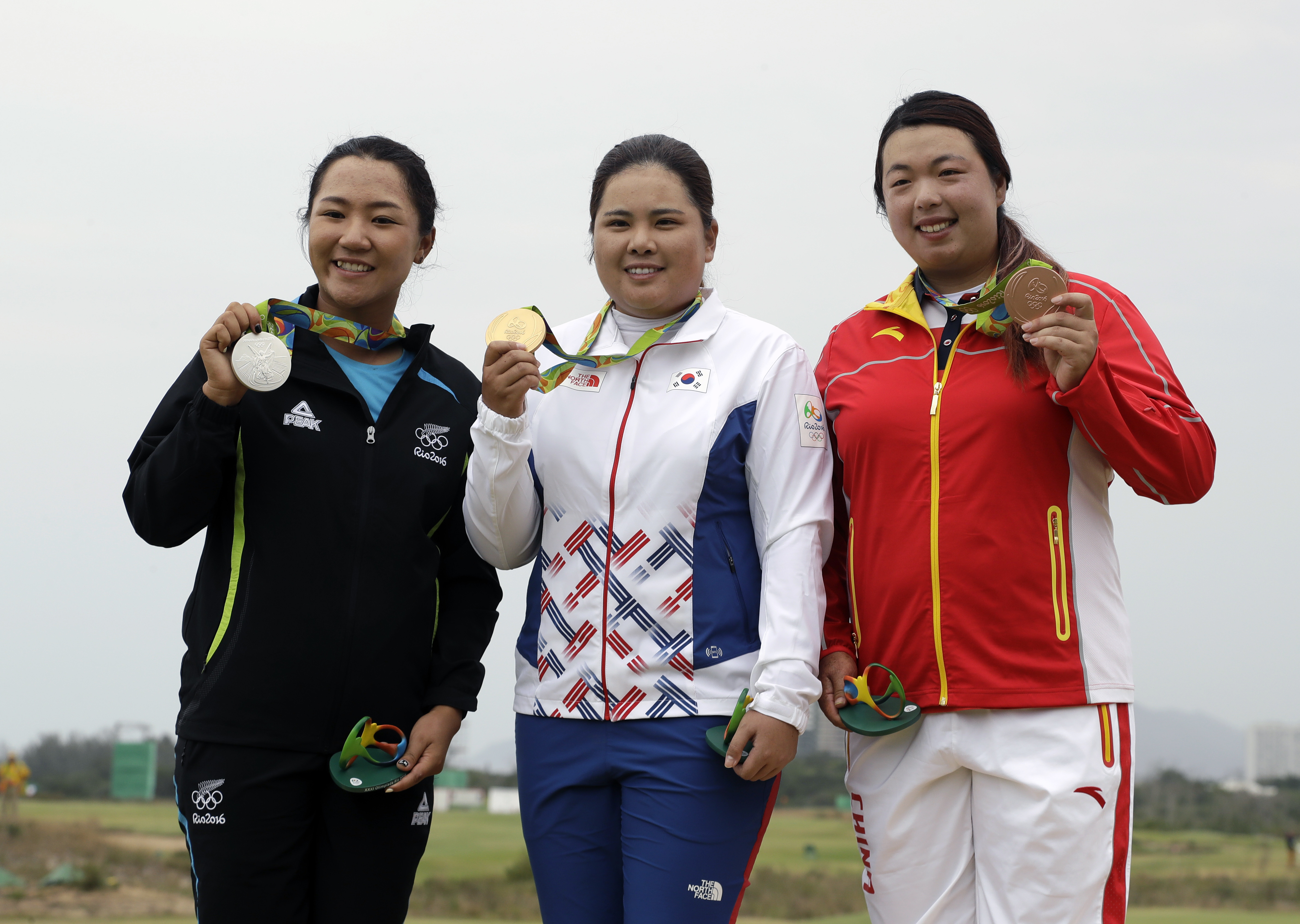 From left to right, silver medalist, Lydia Ko of New Zealand, gold medalist Inbee Park of South Korea, and bronze medalist Shanshan Feng of China, show their medals after the final round of the women's golf event at the 2016 Summer Olympics in Rio de Jane
