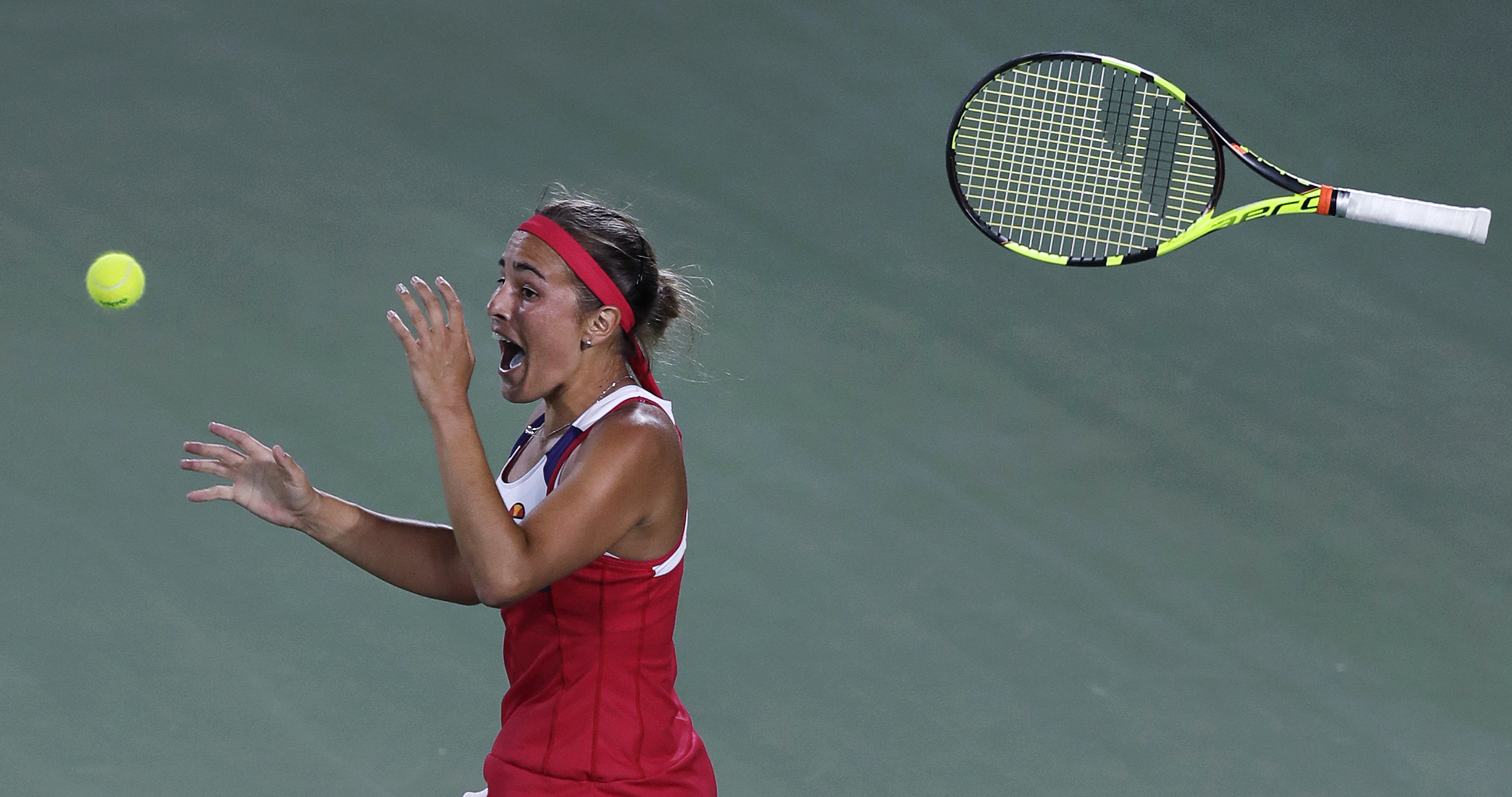FILE - In this Aug. 13, 2016 file photo, Monica Puig, of Puerto Rico, tosses her racquet and celebrates after winning the gold medal against Angelique Kerber, of Germany, during the final round at the 2016 Summer Olympics in Rio de Janeiro, Brazil. (AP Ph