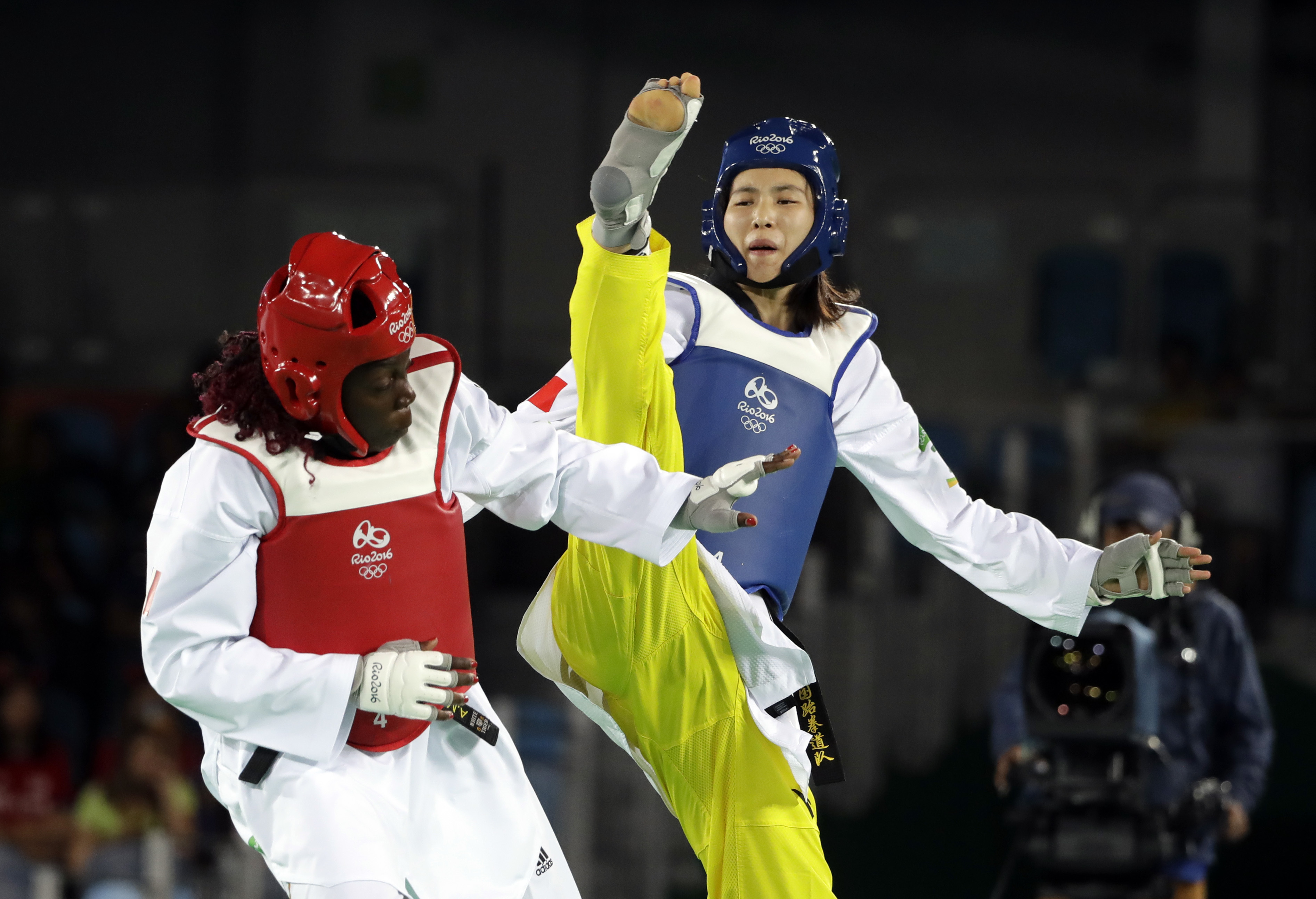 Zheng Shuyin of China, right, and Gwladys Epangue of France compete in a women's over 67-kg quarterfinal Taekwondo event at the 2016 Summer Olympics in Rio de Janeiro, Brazil, Saturday, Aug. 20, 2016. (AP Photo/Marcio Jose Sanchez)