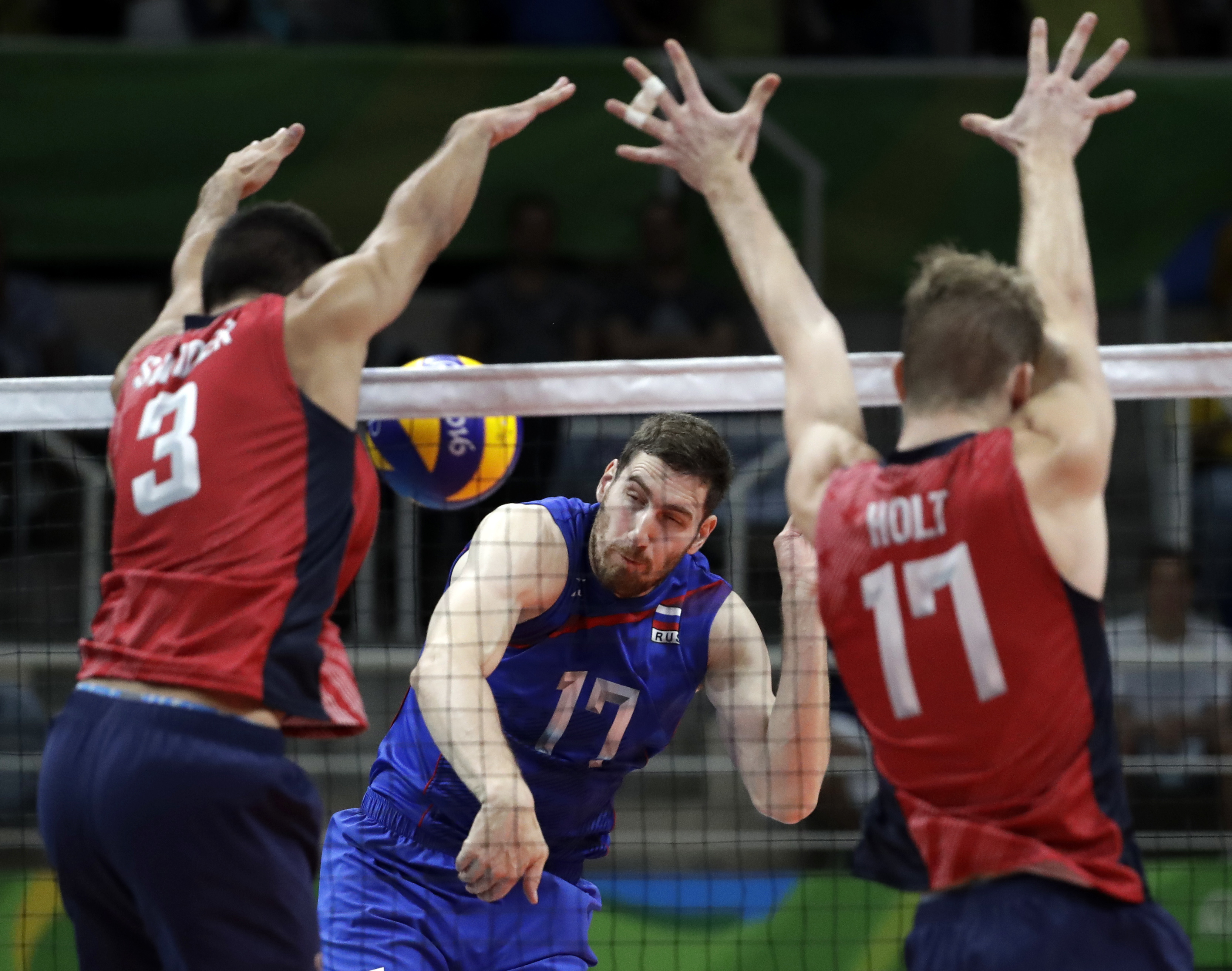 Russia's Maxim Mikhaylov (17) has his shot blocked by United States' Taylor Sander (3) and Maxwell Holt (17) during a men's bronze medal volleyball match at the 2016 Summer Olympics in Rio de Janeiro, Brazil, Sunday, Aug. 21, 2016. (AP Photo/Jeff Roberson