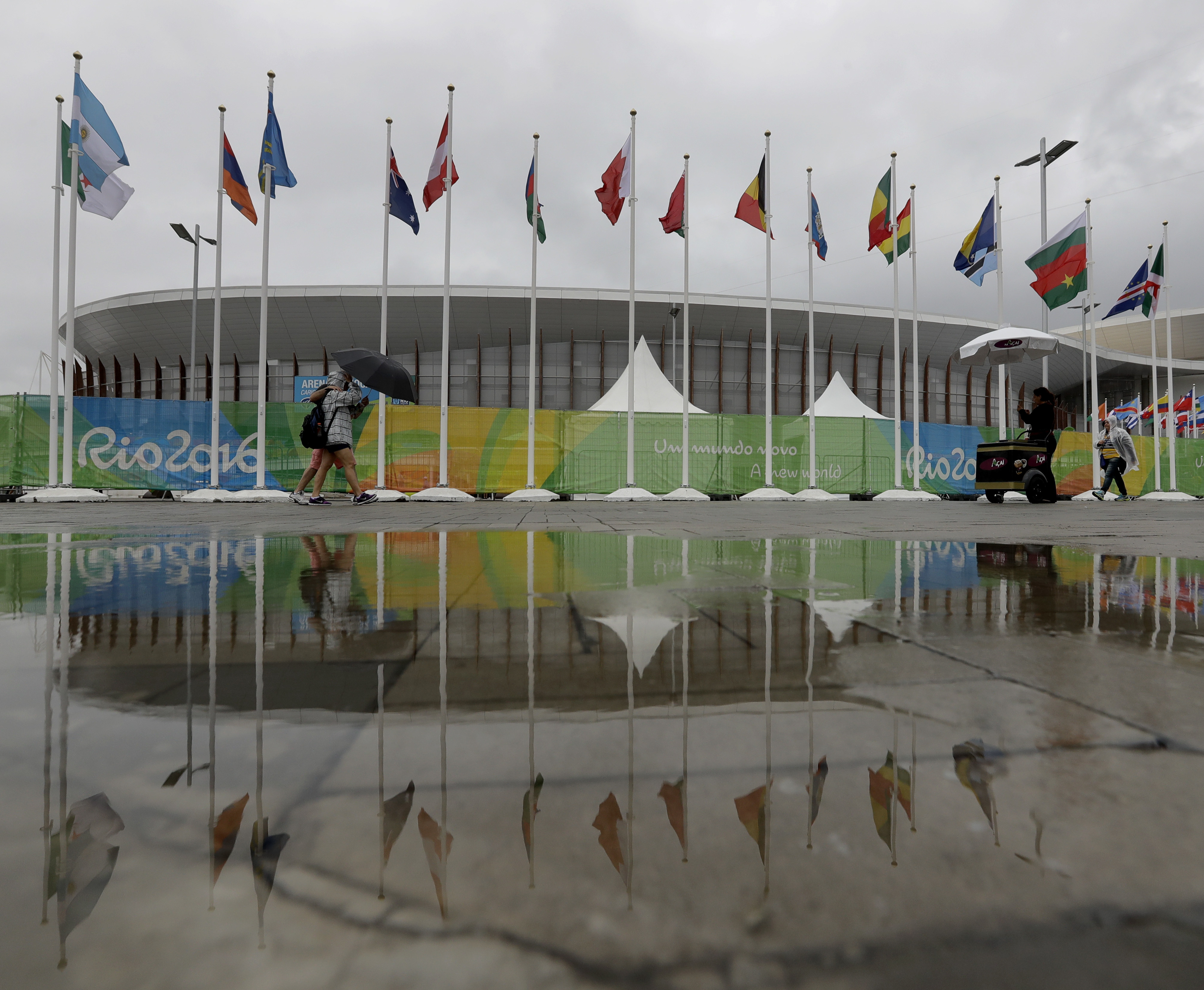 FILE - In this Aug. 10, 2016 file photo, people walk through Olympic Park in the rain at the 2016 Summer Olympics in Rio de Janeiro, Brazil. A recession and declining real estate market may spoil Rios plans to turn the heart of the Olympic Games into a bu