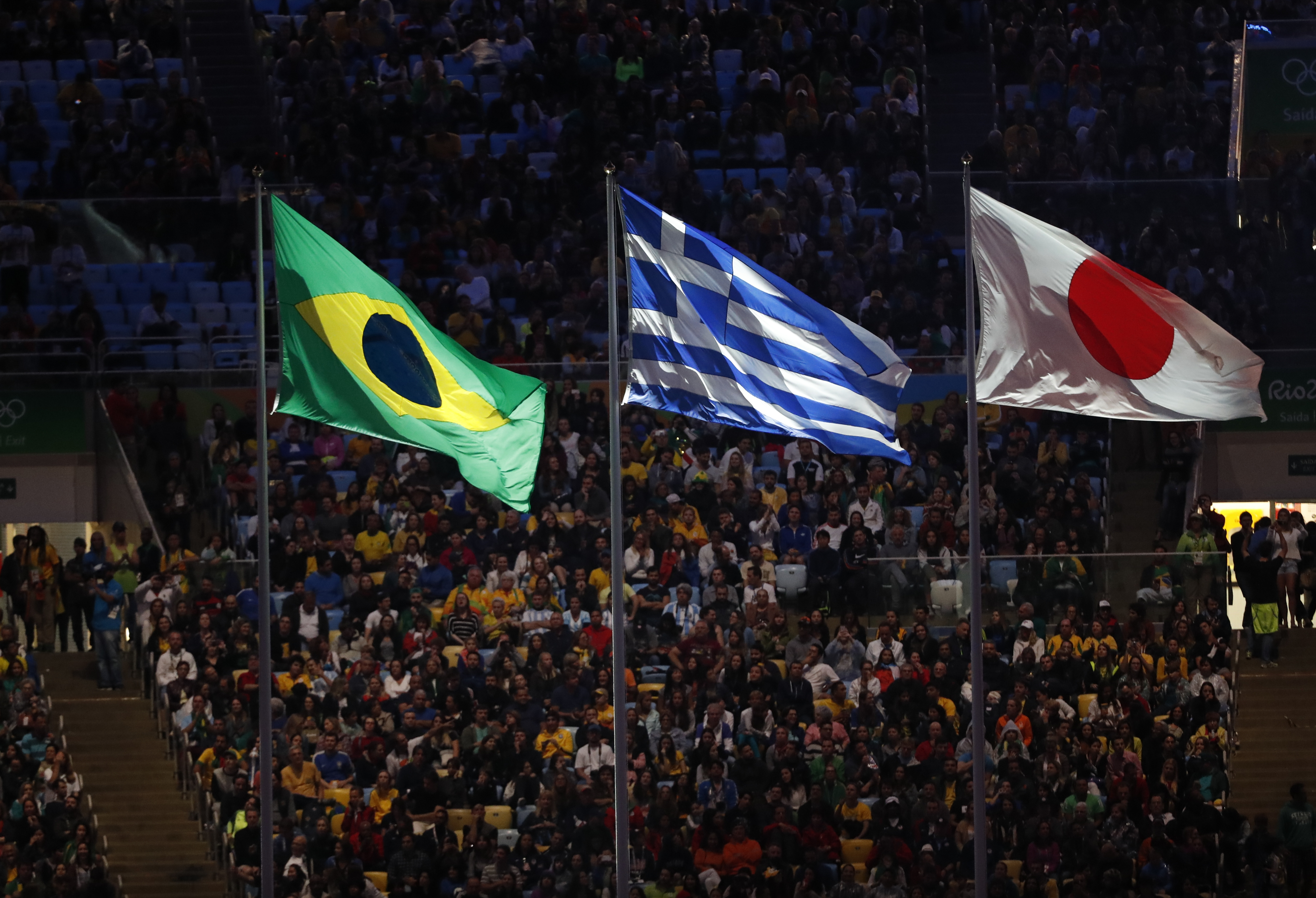 The flags of Brazil, Greece and Japan fly during the closing ceremony for the Summer Olympics inside Maracana stadium in Rio de Janeiro, Brazil, Sunday, Aug. 21, 2016. (AP Photo/Vincent Thian)