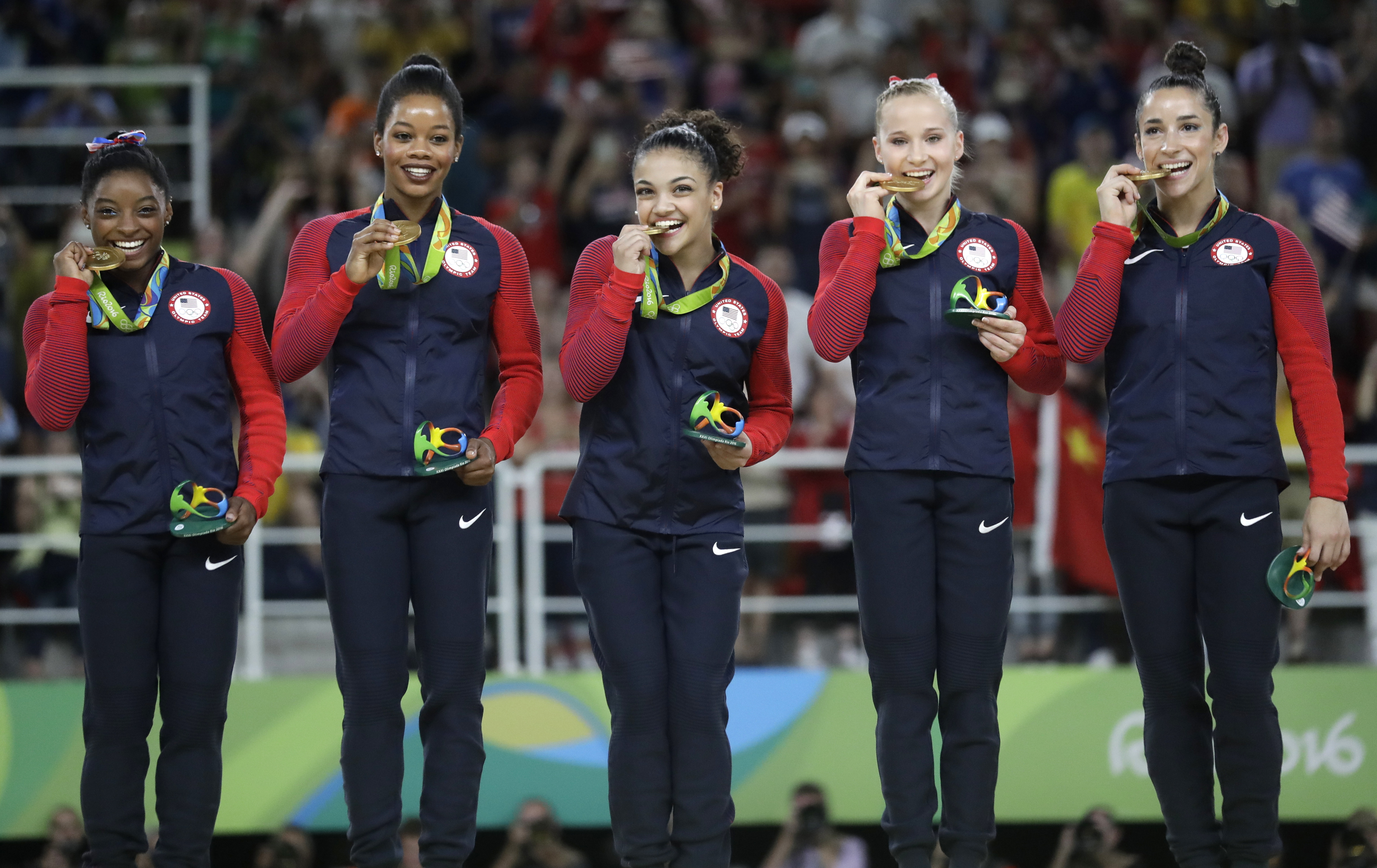 FILE - In this Aug. 9, 2016 file photo, U.S. gymnasts, from left, Simone Biles, Gabrielle Douglas, Lauren Hernandez, Madison Kocian and Aly Raisman hold their gold medals during the medal ceremony for the artistic gymnastics women's team at the 2016 Summe