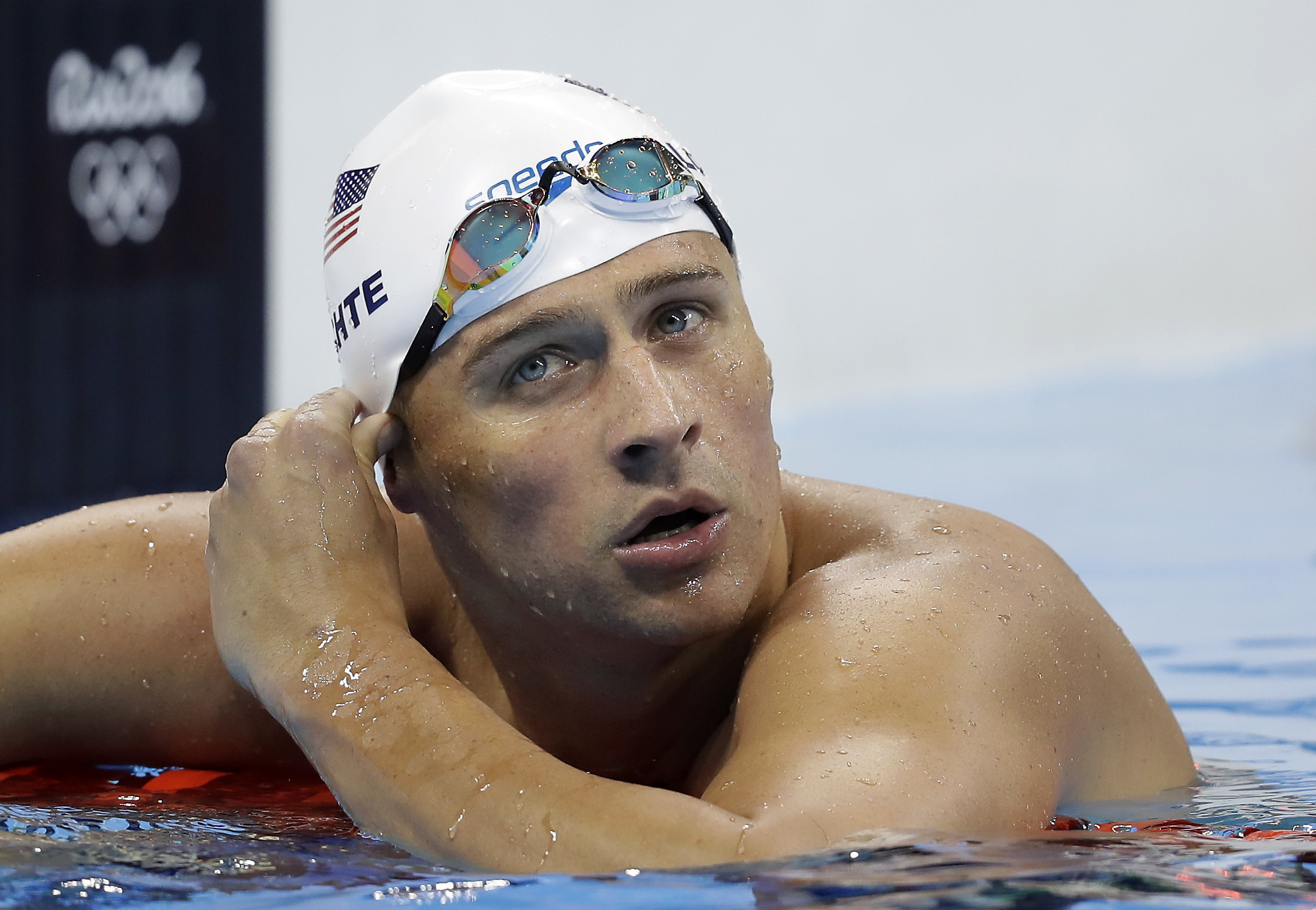 FILE - In this Tuesday, Aug. 9, 2016, file photo, United States' Ryan Lochte checks his time in a men's 4x200-meter freestyle heat at the 2016 Summer Olympics, in Rio de Janeiro, Brazil. Lochte is banned from swimming through next June and will forfeit $1