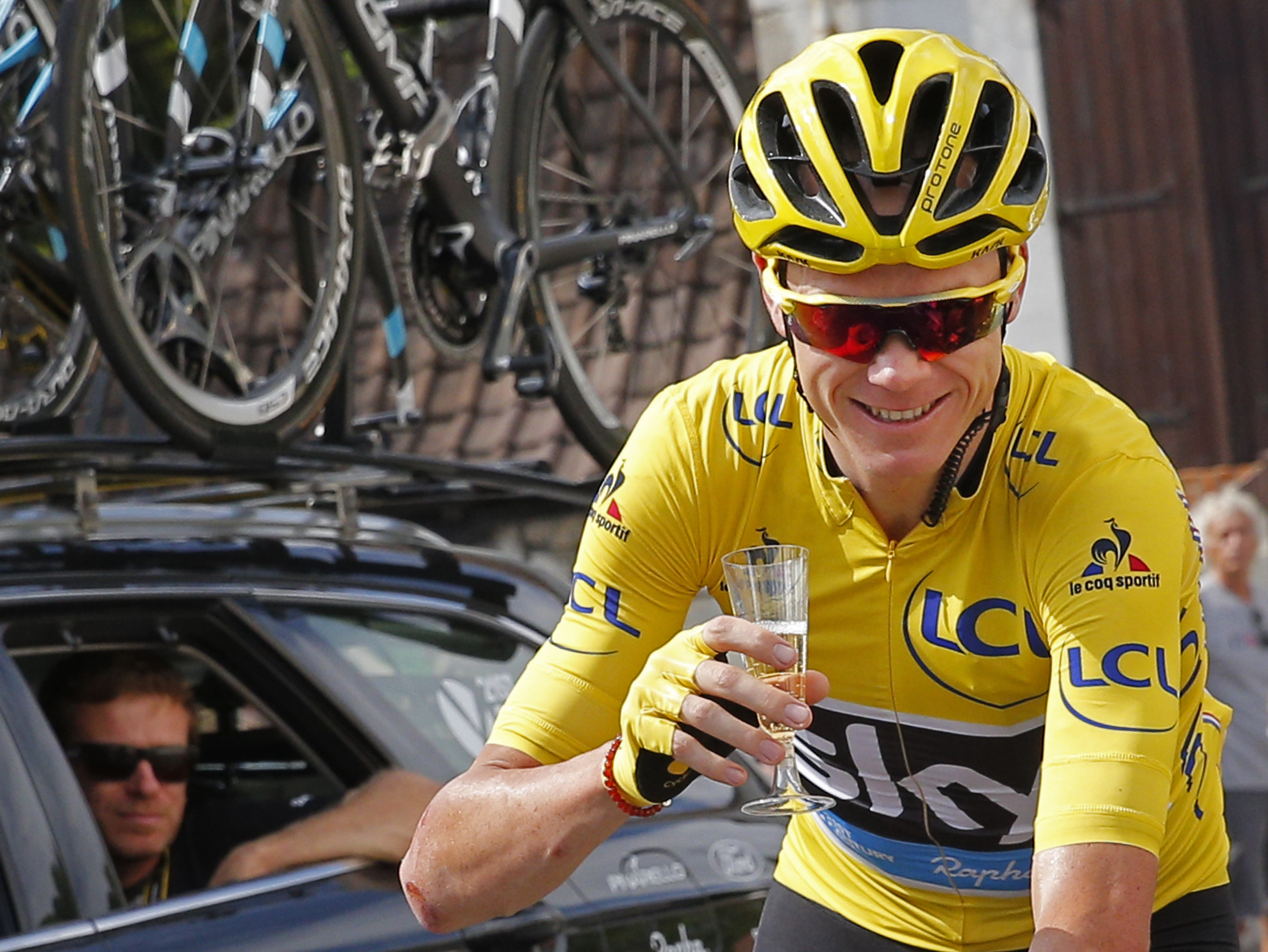 FILE - This is a Sunday, July 24, 2016  file photo of Britain's Chris Froome, wearing the overall leader's yellow jersey, celebrates with a glass of champagne during the twenty-first stage of the Tour de France  in Paris. Three-time Tour de France winner