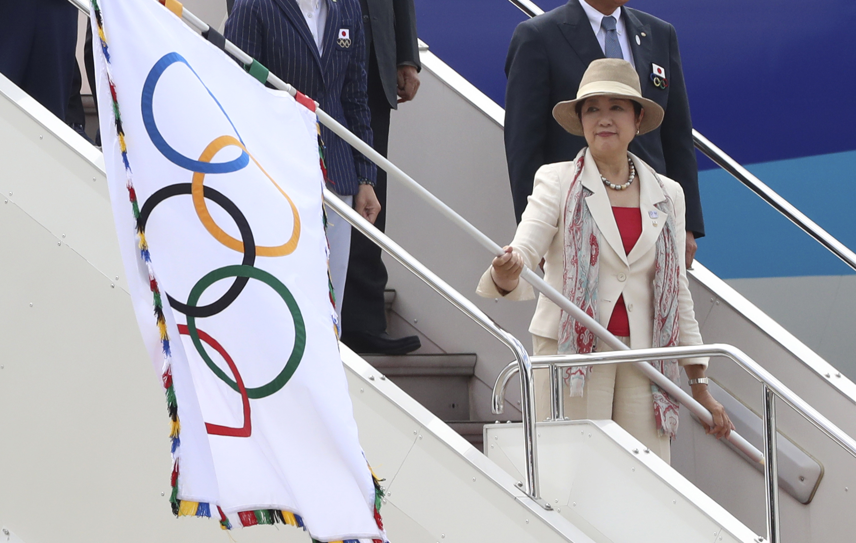 FILE - In this Aug. 24, 2016 file photo, Tokyo Gov. Yuriko Koike waves the Olympic flag upon arrival of the flag at Haneda international airport in Tokyo. Koike expects the 2020 Paralympics to make Japan's capital more accessible for people with disabilit