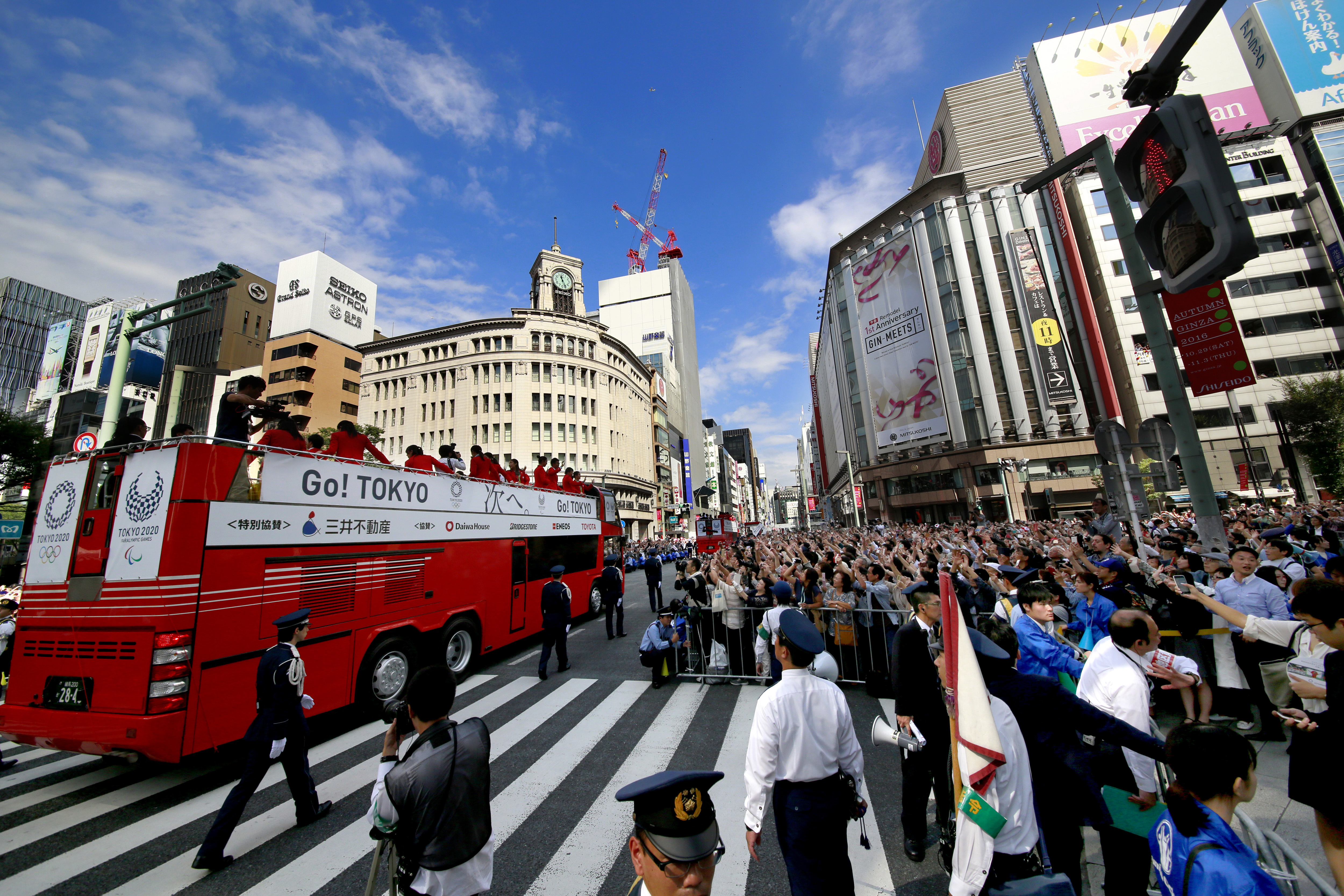 In this Friday, Oct. 7, 2016 photo, people wave at Japanese medalists of Rio de Janeiro Olympics and Paralympics during a parade in Tokyo's Ginza district. Some 90 medalists took part in the 2.5 kilometers (1.6 mile) motorcade through streets in Tokyo, th