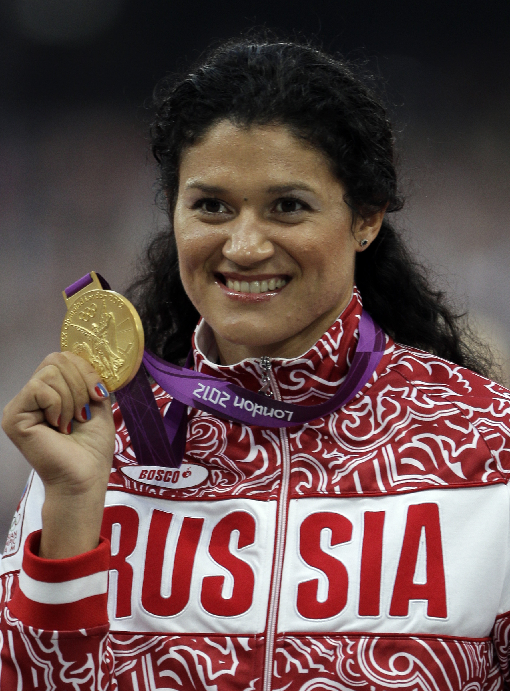 FILE - In this Aug. 11, 2012 file photo Russia's Tatyana Lysenko poses with her gold medal for the women's hammer throw during the athletics in the Olympic Stadium at the 2012 Summer Olympics in London. Lysenko has been stripped of her gold medal from the