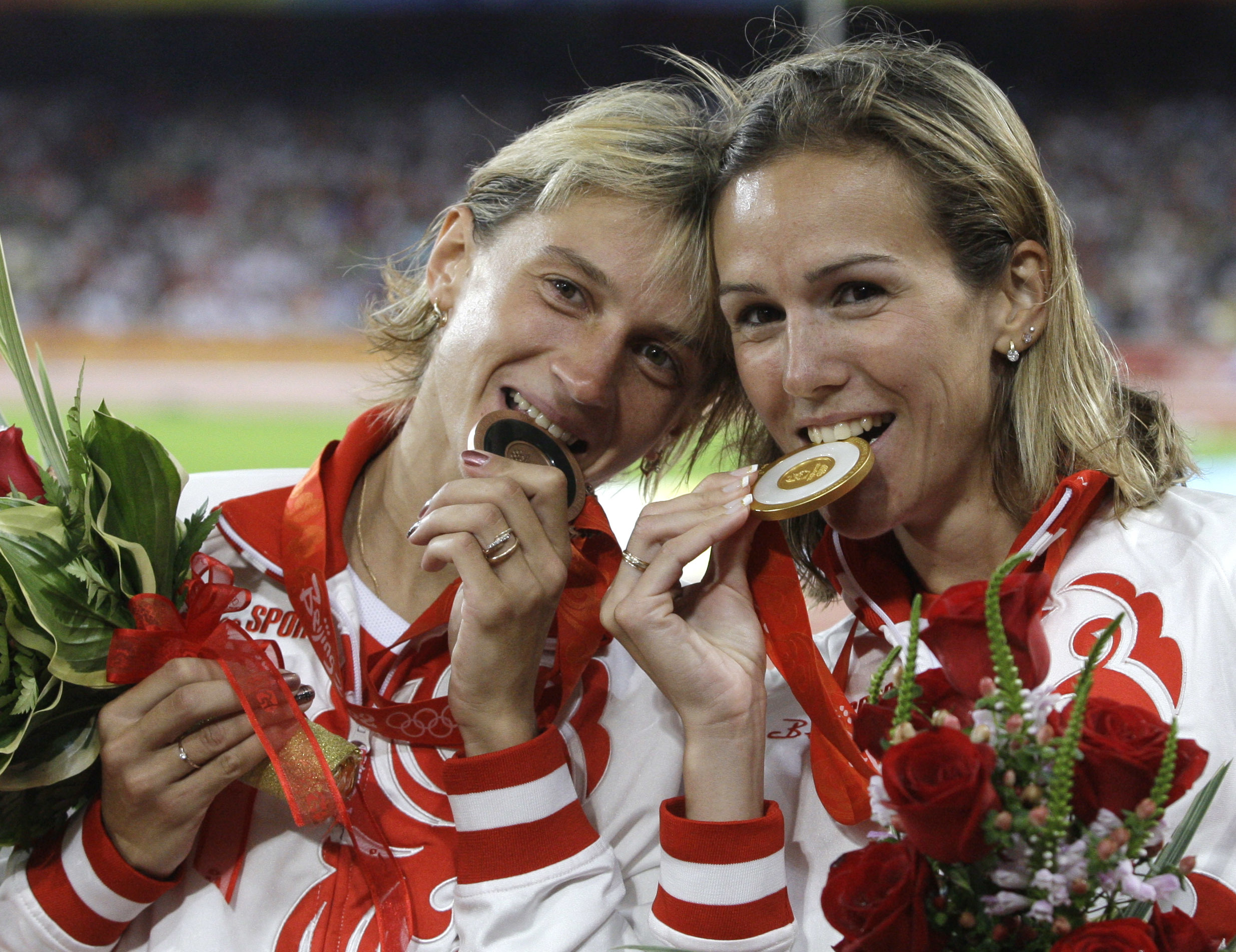 FILE - In this Sunday, Aug. 17, 2008 file photo, Russia's gold medal winner Gulnara Galkina-Samitova, left, and bronze medal winner Ekaterina Volkova bite their medals after the women's 3000-meter steeplechase at the Beijing 2008 Olympics in Beijing. Nine