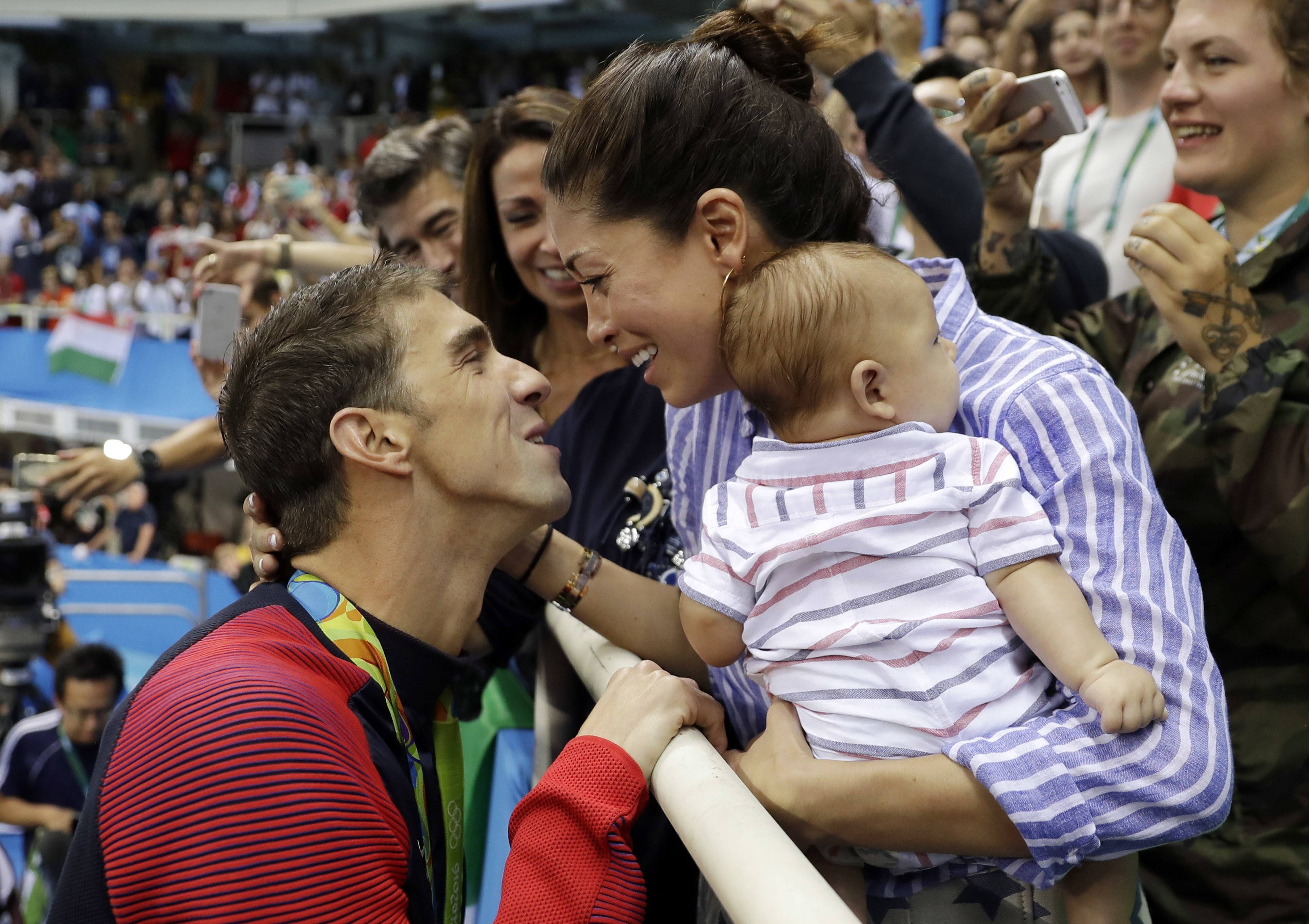 FILE - In this Aug. 9, 2016, file photo, United States' swimmer Michael Phelps celebrates winning his gold medal in the men's 200-meter butterfly with his fiance Nicole Johnson and baby Boomer during the swimming competitions at the 2016 Summer Olympics,