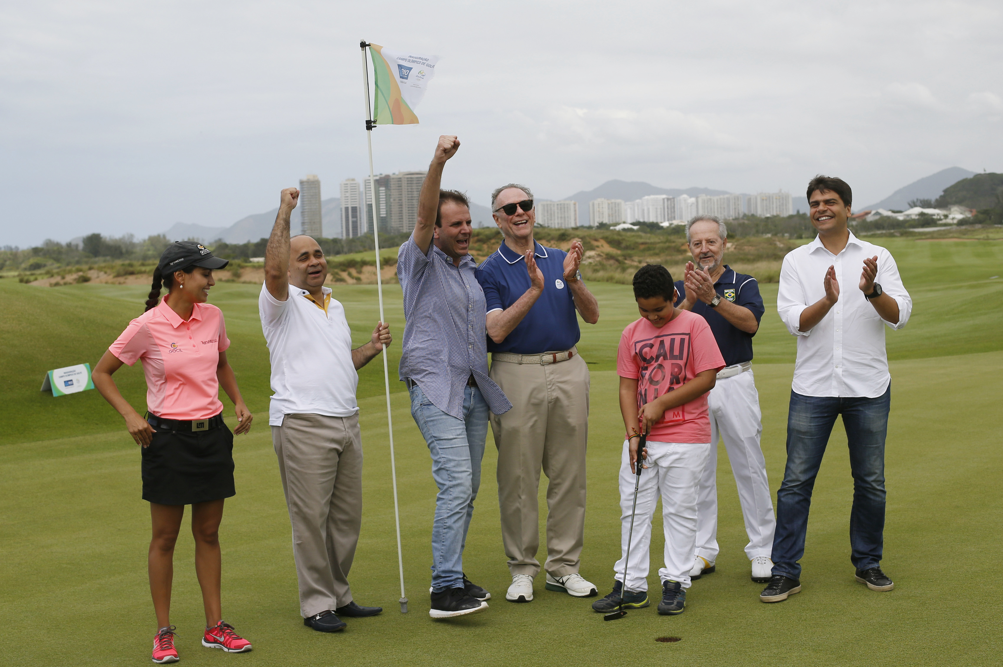 FILE - In this Nov. 22, 2015 file photo, Rio de Janeiro Mayor Eduardo Paes, third left, and Brazil Olympic Committee President Carlos Nuzman, center, celebrate during a ceremony at the Olympic Golf Course in Rio de Janeiro, Brazil. A Brazilian judge has f