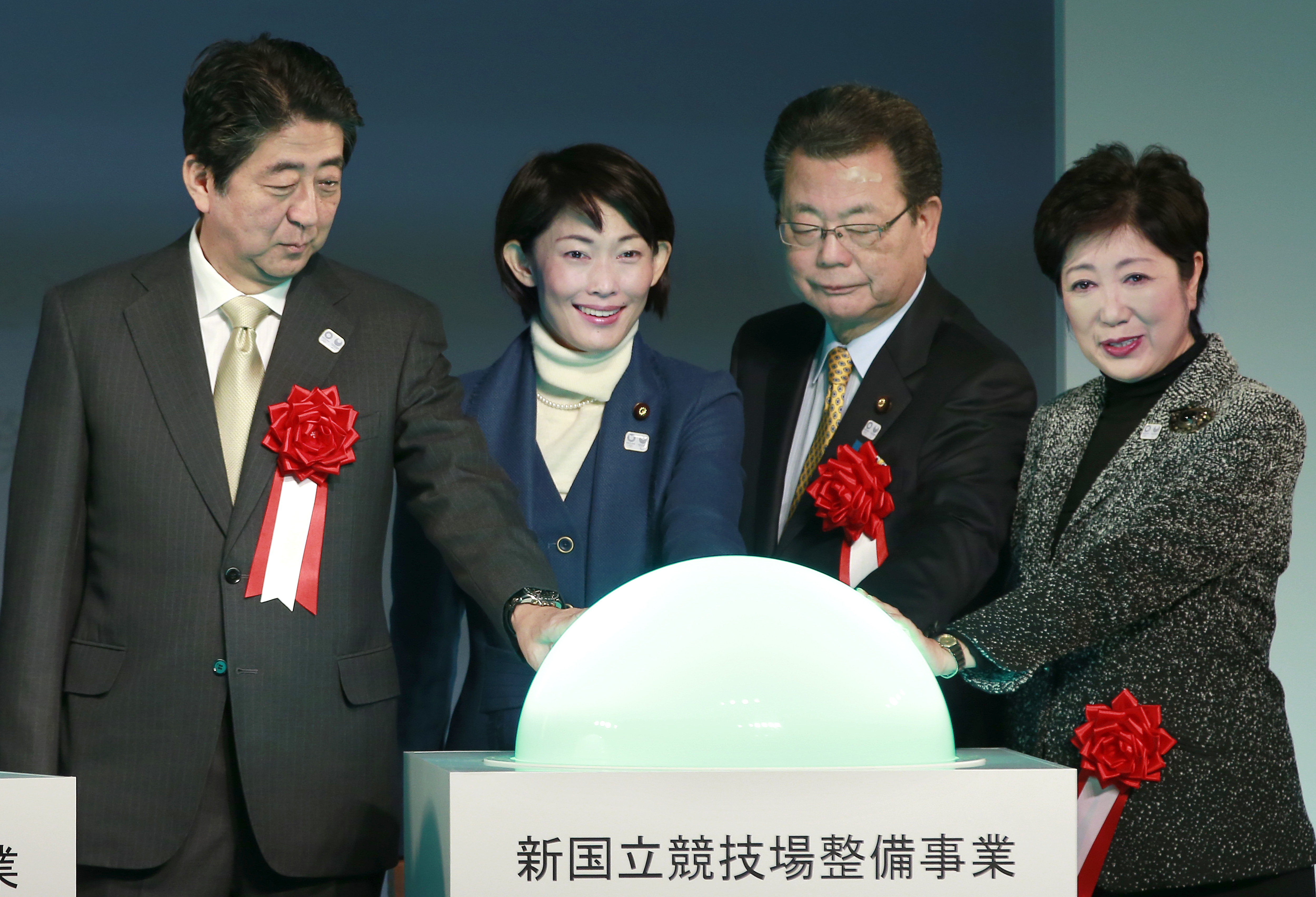 From left, Japanese Prime Minister Shinzo Abe, Olympic Minister Tamayo Marukawa, Cabinet Office Vice Minister Toshiei Mizuochi, and Tokyo Gov. Yuriko Koike turn on the switch during a groundbreaking ceremony of new national stadium in Tokyo, Sunday, Dec.
