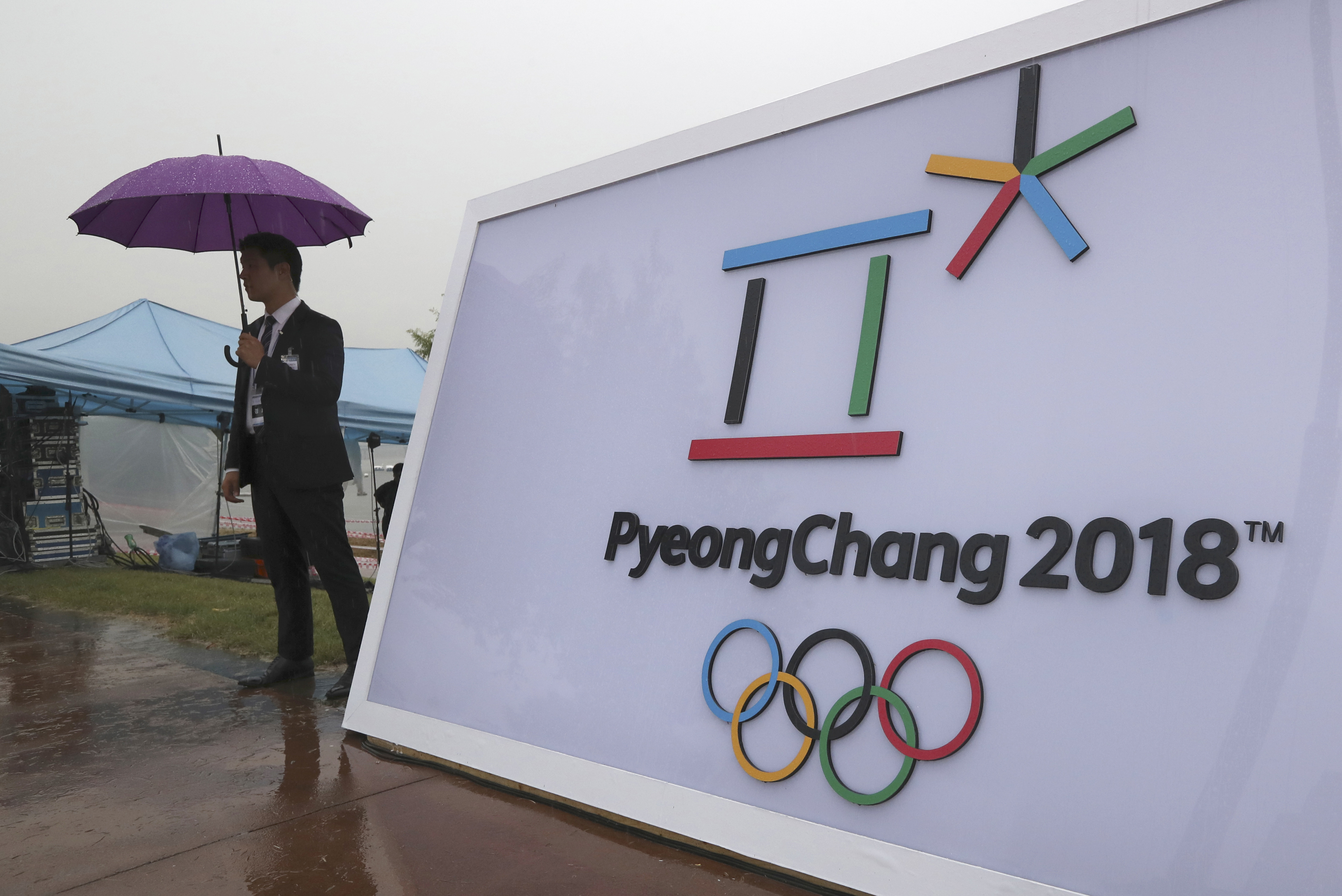 FILE - In this Sept. 27, 2016 file photo, security personnel stands by a logo of the 2018 PyeongChang Olympic Winter Games before an event to mark the start of the 500-day countdown in Seoul, South Korea. The head of analysis for Gracenote, a US-based spo