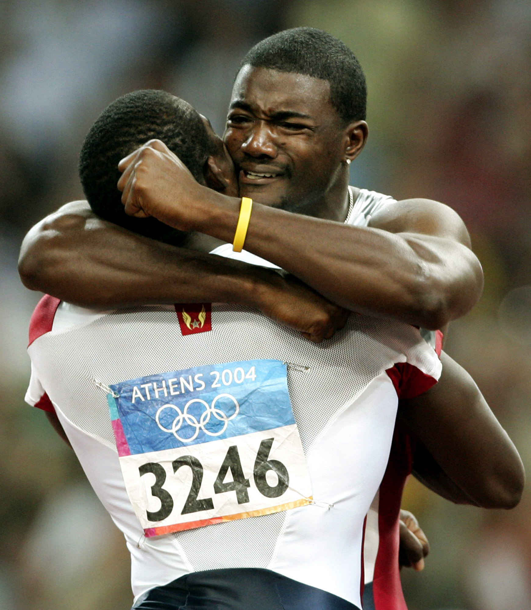FILE - In this Aug. 22, 2004, file photo, Justin Gatlin, of the United States, is congratulated by compatriot Shawn Crawford (3246) after Gatlin won the gold medal in the 100 meters at the Olympic Stadium during the 2004 Olympic Games in Athens. Crawford
