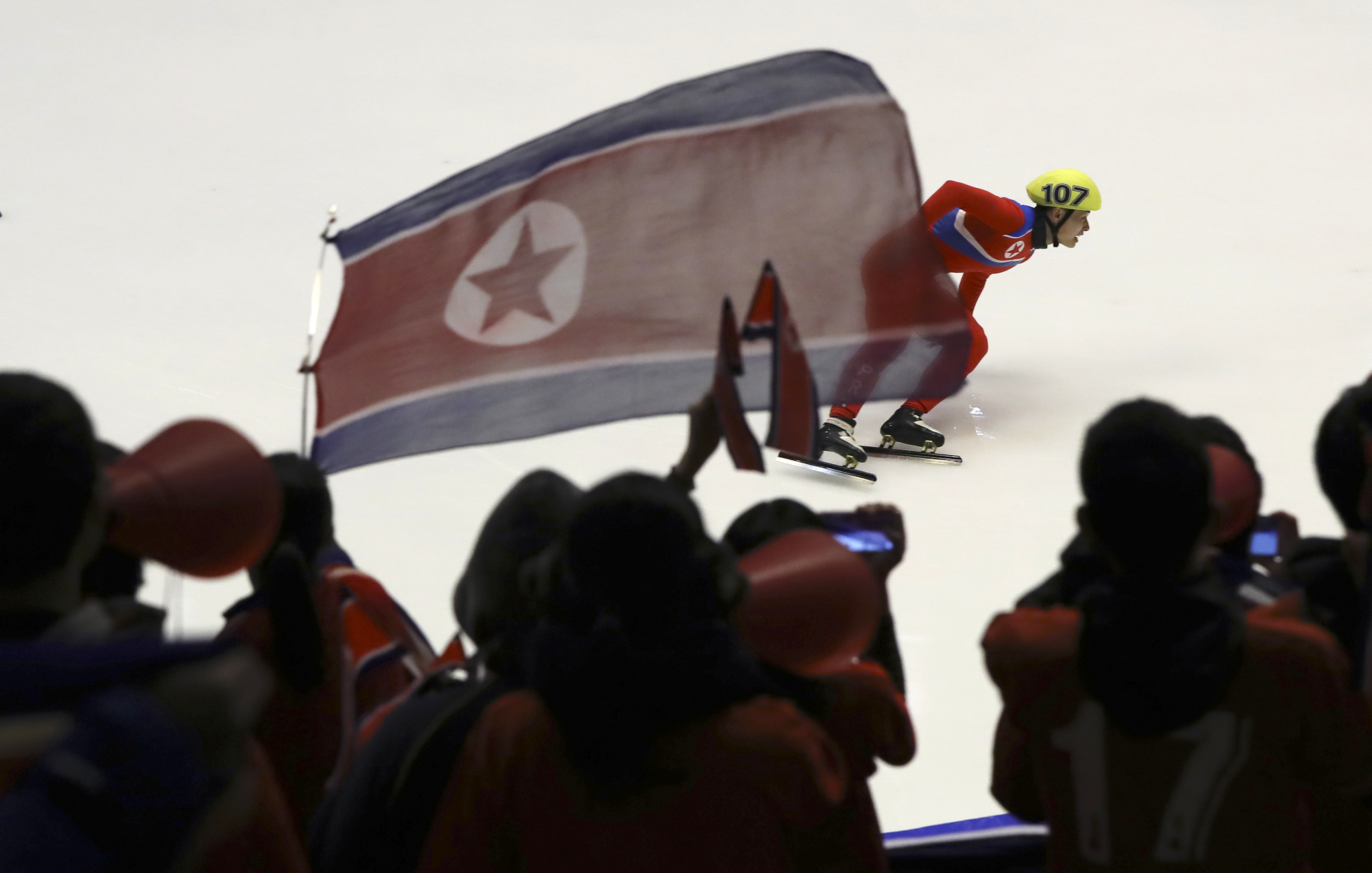 Kim Chol Gwang of North Korea competes as fans of the North Korean team chant during the men's 500 meters heat of short track speed skating competition at the Asian Winter Games at Makomanai Indoor Skating Rink in Sapporo, northern Japan, Tuesday, Feb. 21