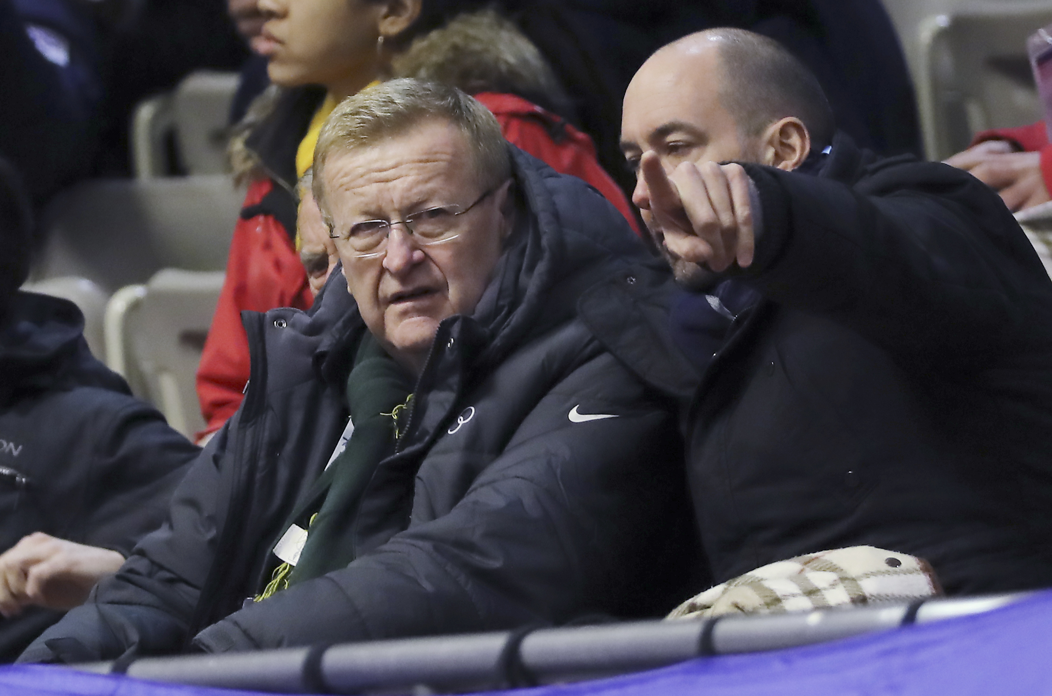 FILE - In this Feb. 20, 2017 file photo, the International Olympic Committee Vice President John Coates, left, looks at a men's 1500 meters heat of short track speed skating competition at the Asian Winter Games at Makomanai Indoor Skating Rink in Sapporo