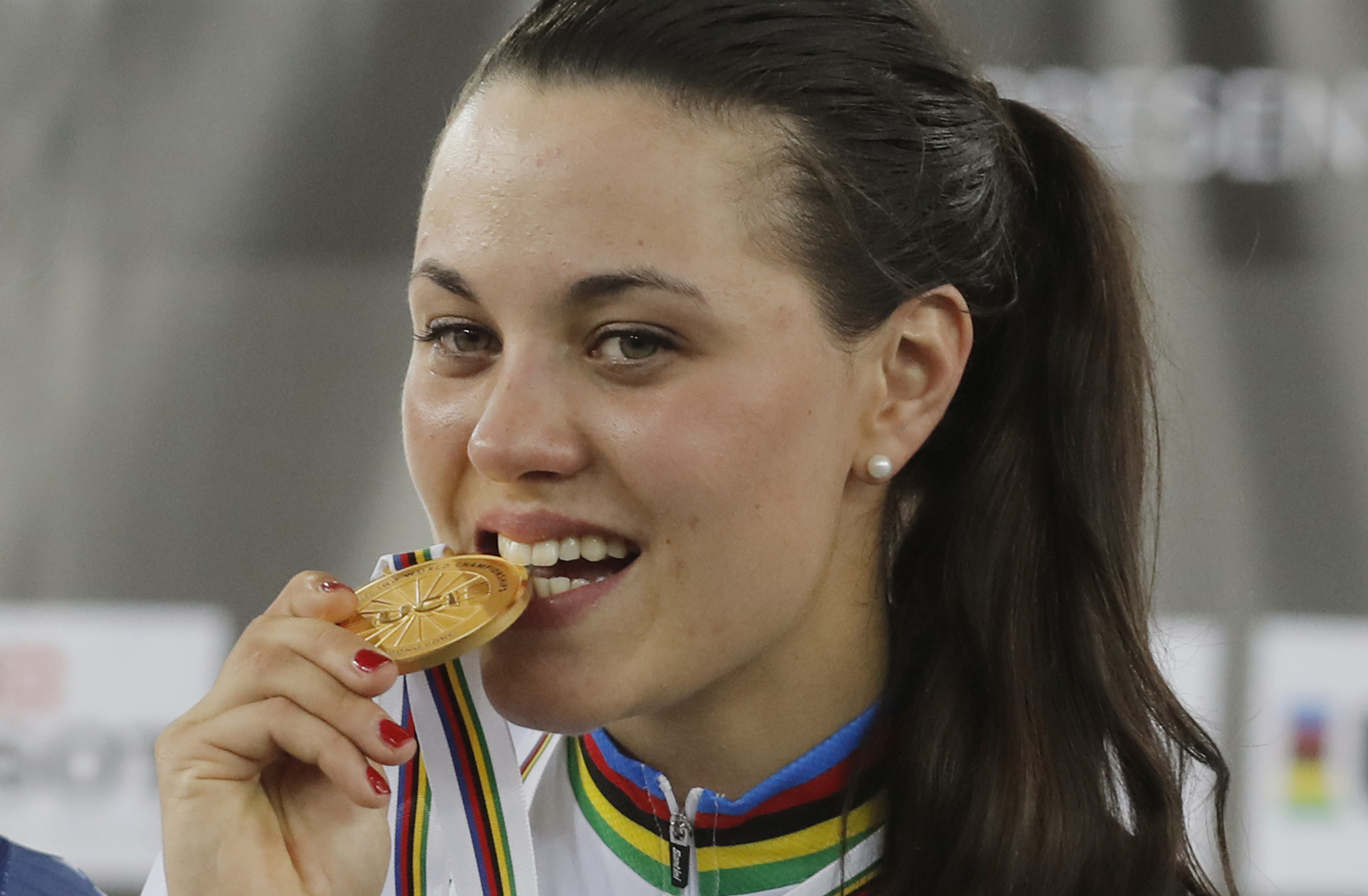 Italy's Rachele Barbieri bites her gold medal on the podium after winning the women's scratch race at the World Track Cycling championships in Hong Kong, Wednesday, April 12, 2017. (AP Photo/Kin Cheung)