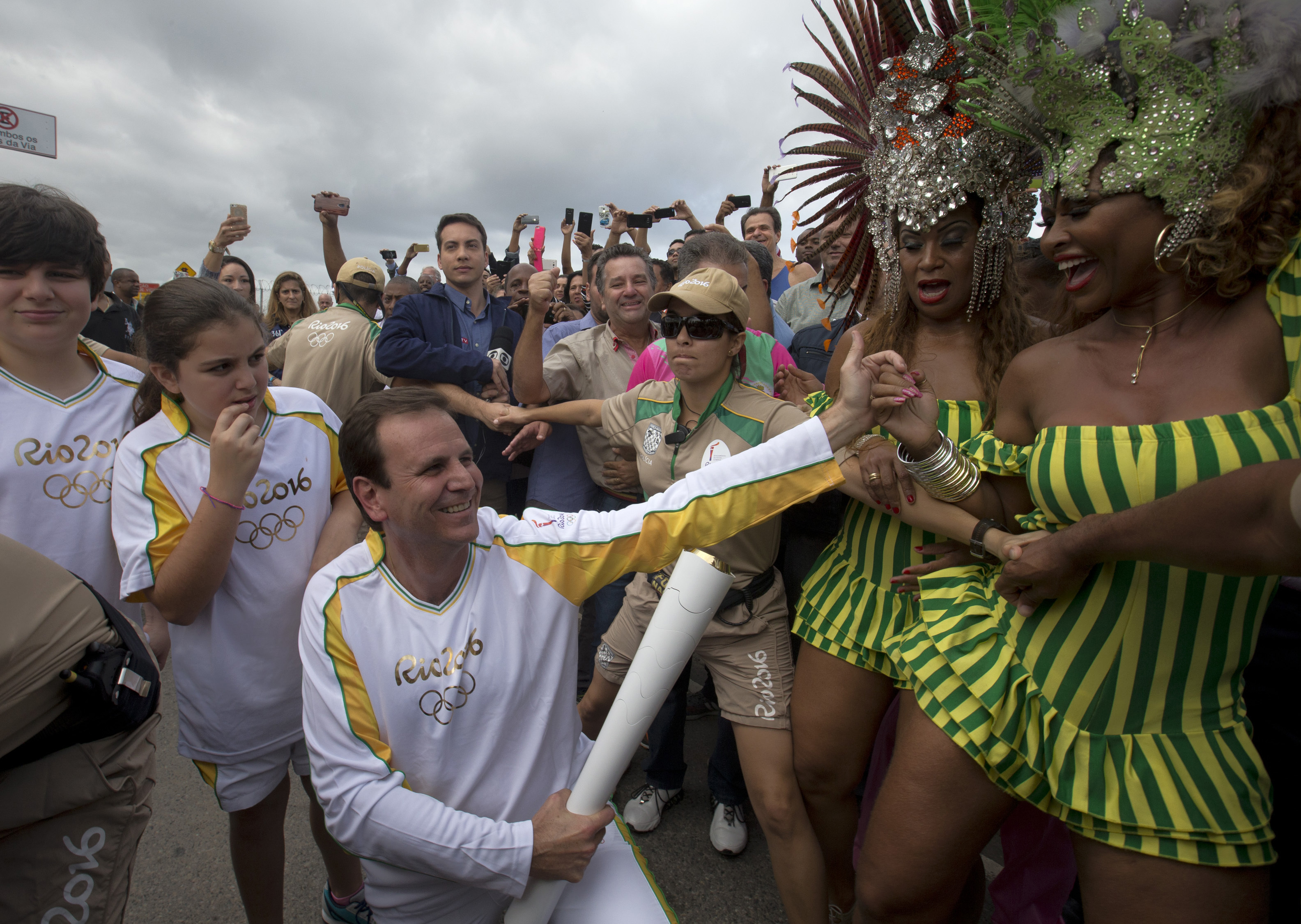 File - In this Aug. 3, 2016 file photo, Rio de Janeiro's Mayor Eduardo Paes, center, holds the Olympic torch, while members of the Mangueira samba school dance, in Rio de Janeiro, Brazil. The former Rio de Janeiro Mayor, the moving force behind organizing