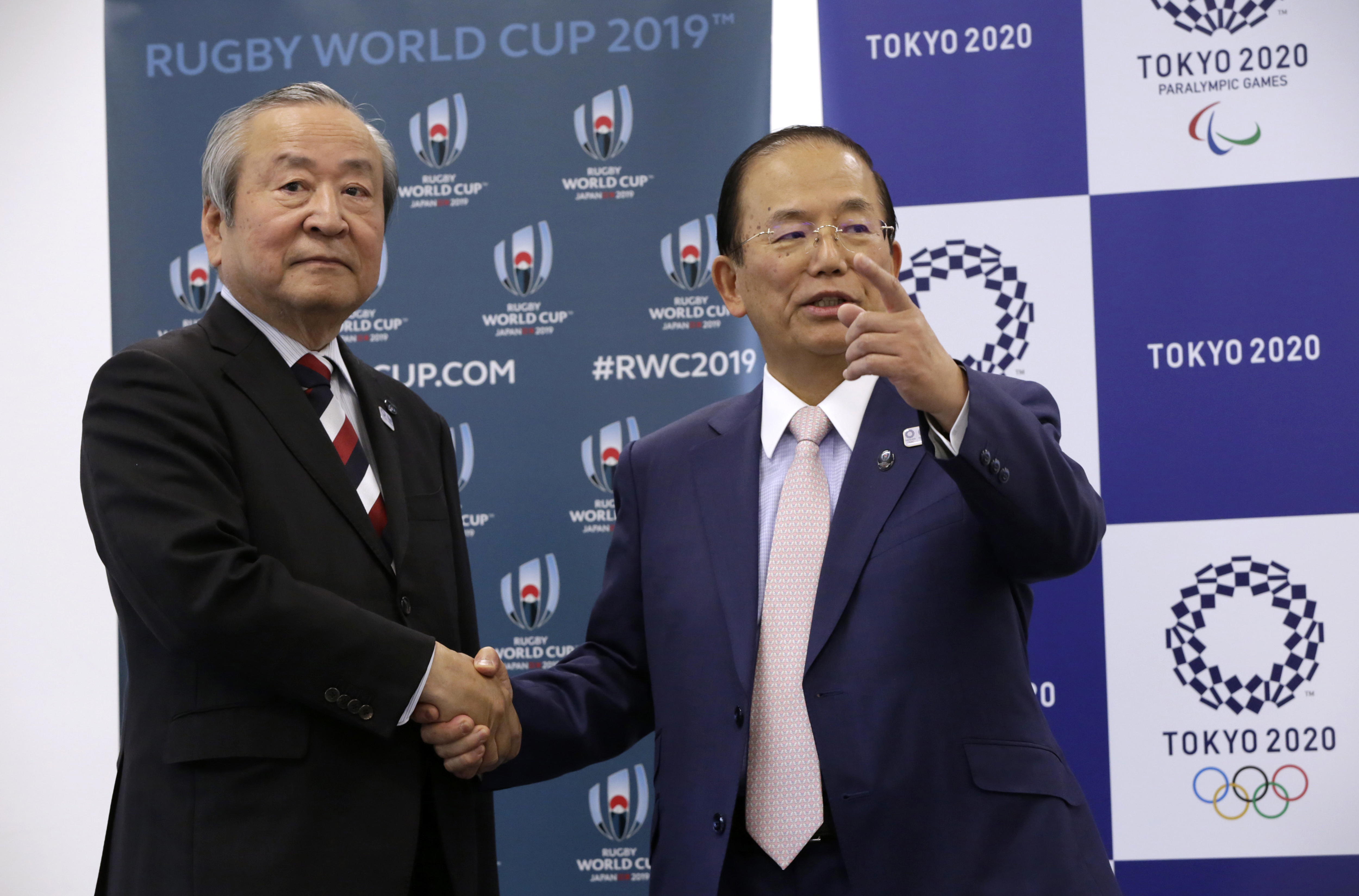 Tokyo 2020 Olympics CEO Toshiro Muto, right, and President and CEO of the 2019 Rugby World Cup Organizing Committee President and CEO Akira Shimazu shake hands after signing a collaborative agreement in Tokyo, Wednesday, April 26, 2017. Organizers of the