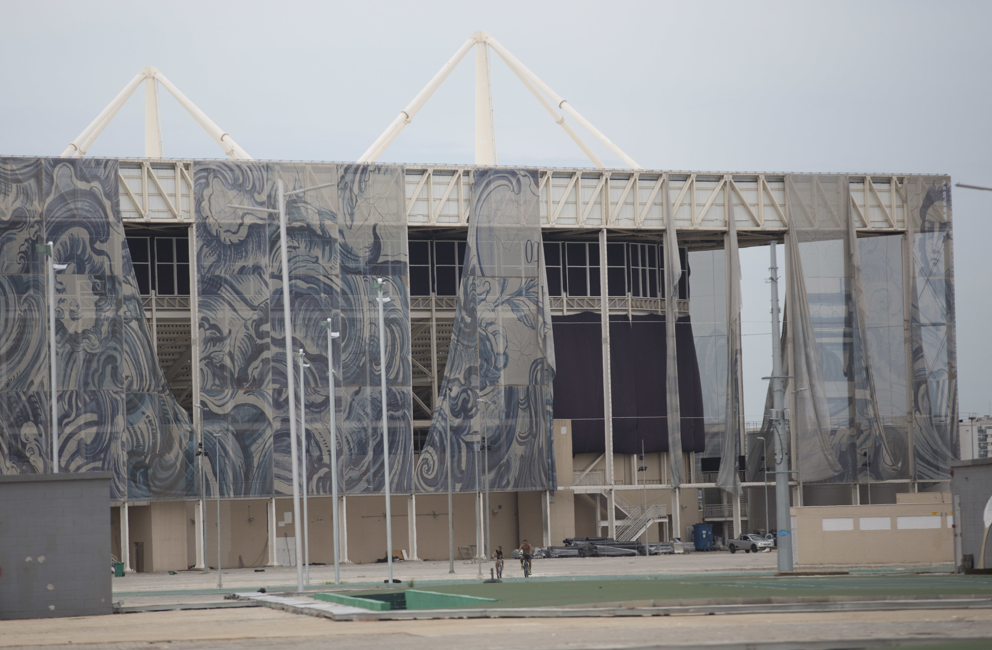 FILE - This Feb. 4, 2017 file photo shows translucent tapestries created by Brazilian artist Adriana Varejao, falling from the exterior of Olympic Aquatic stadium inside Olympic Park in Rio de Janeiro, Brazil. Many of the Rio Olympics venues are empty, bo