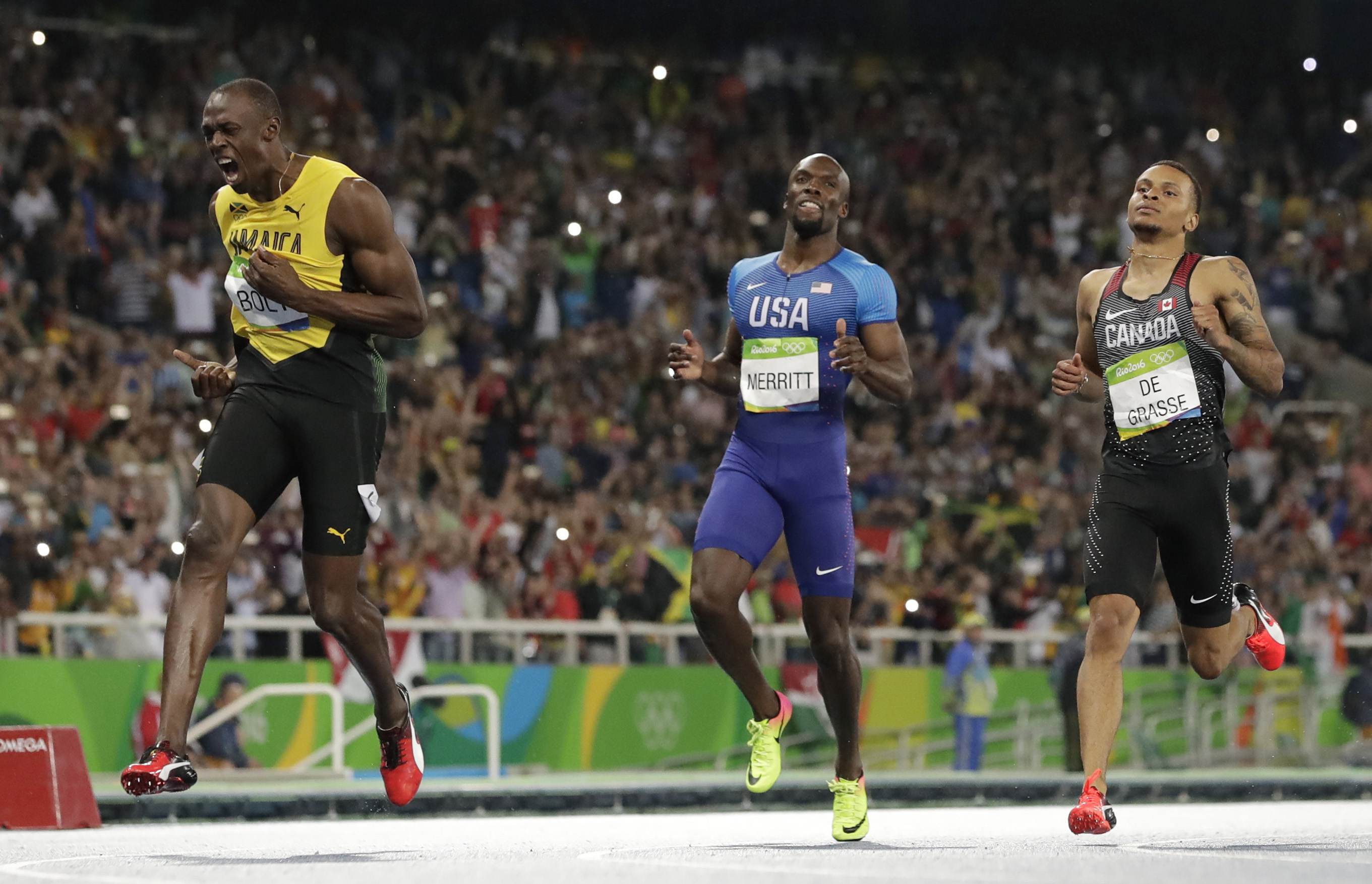 FILE - In this Thursday, Aug. 18, 2016 file photo, Usain Bolt from Jamaica, left, crosses the line to win the gold medal in the men's 200-meter final ahead of second placed Canada's Andre De Grasse, right, during the athletics competitions of the 2016 Sum