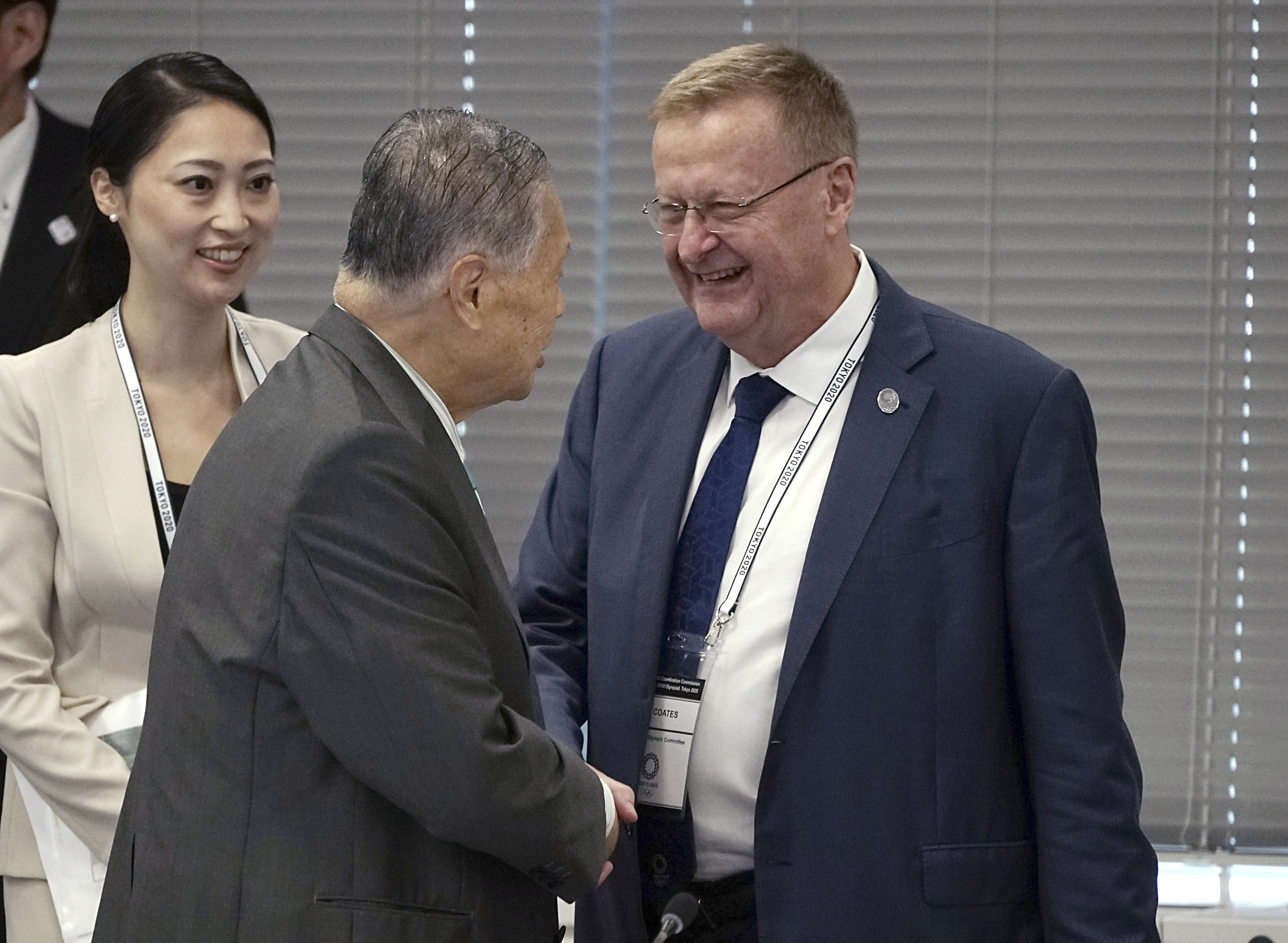 International Olympic Committee (IOC) Vice President John Coates, right, and Tokyo 2020 Olympics President Yoshiro Mori, center, shake hands prior to the IOC Coordination Commission opening plenary for the Olympic Games Tokyo 2020 in Tokyo Wednesday, June