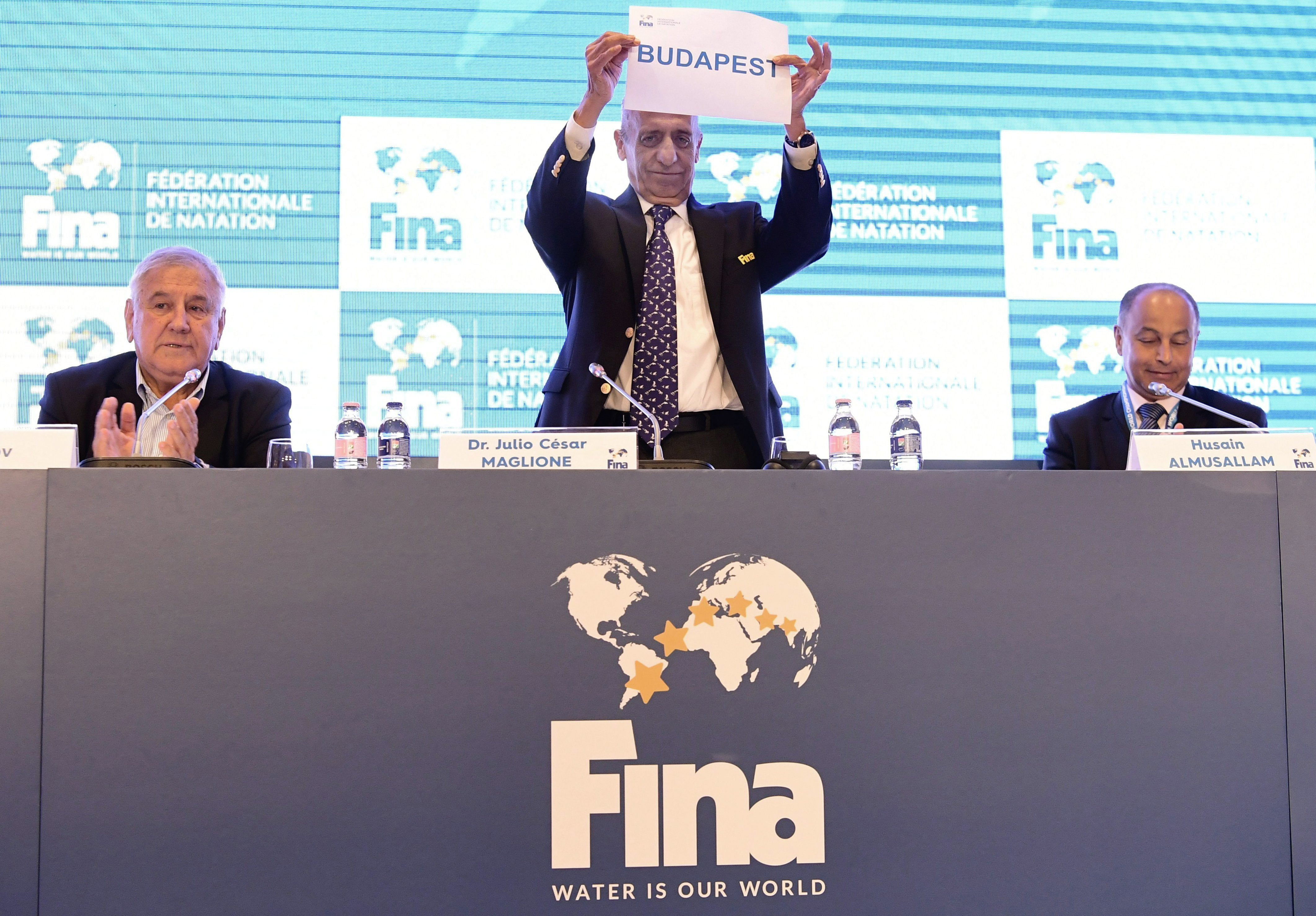 President of the International Swimming Federation, FINA, Julio C. Maglione raises a sheet of paper bearing the name of the Hungarian capital between Sports Minister of Tatarstan Vladimir Leonov, left, and FINA Vice President Husain Al-Musallam of Kuwait