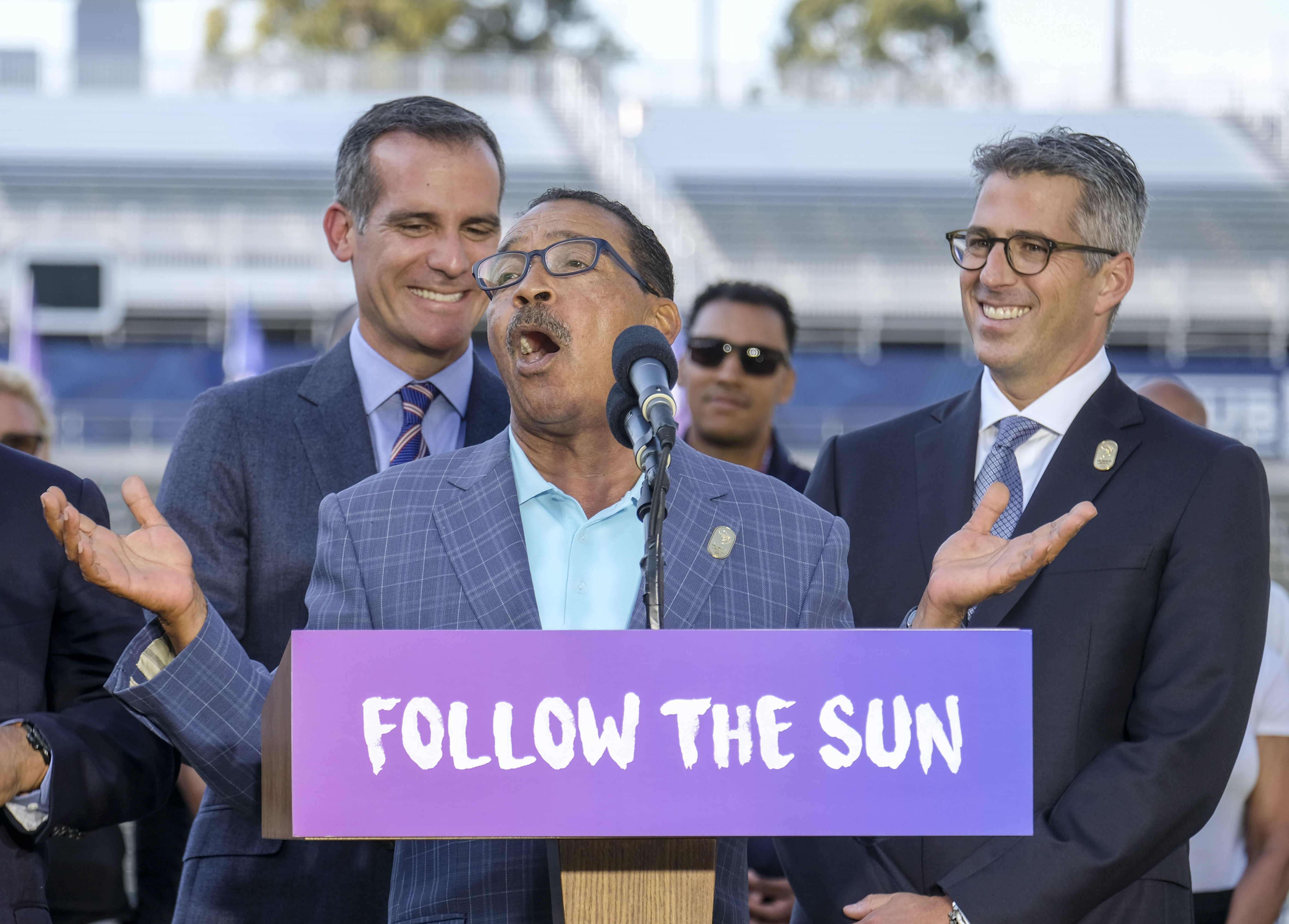 Los Angeles Mayor Eric Garcetti, left, and L.A. Olympic Committee leader Casey Wasserman, right, react as City Council President Herb Wesson speaks during a press conference to make an announcement for the city to host the Olympic Games and Paralympic Gam