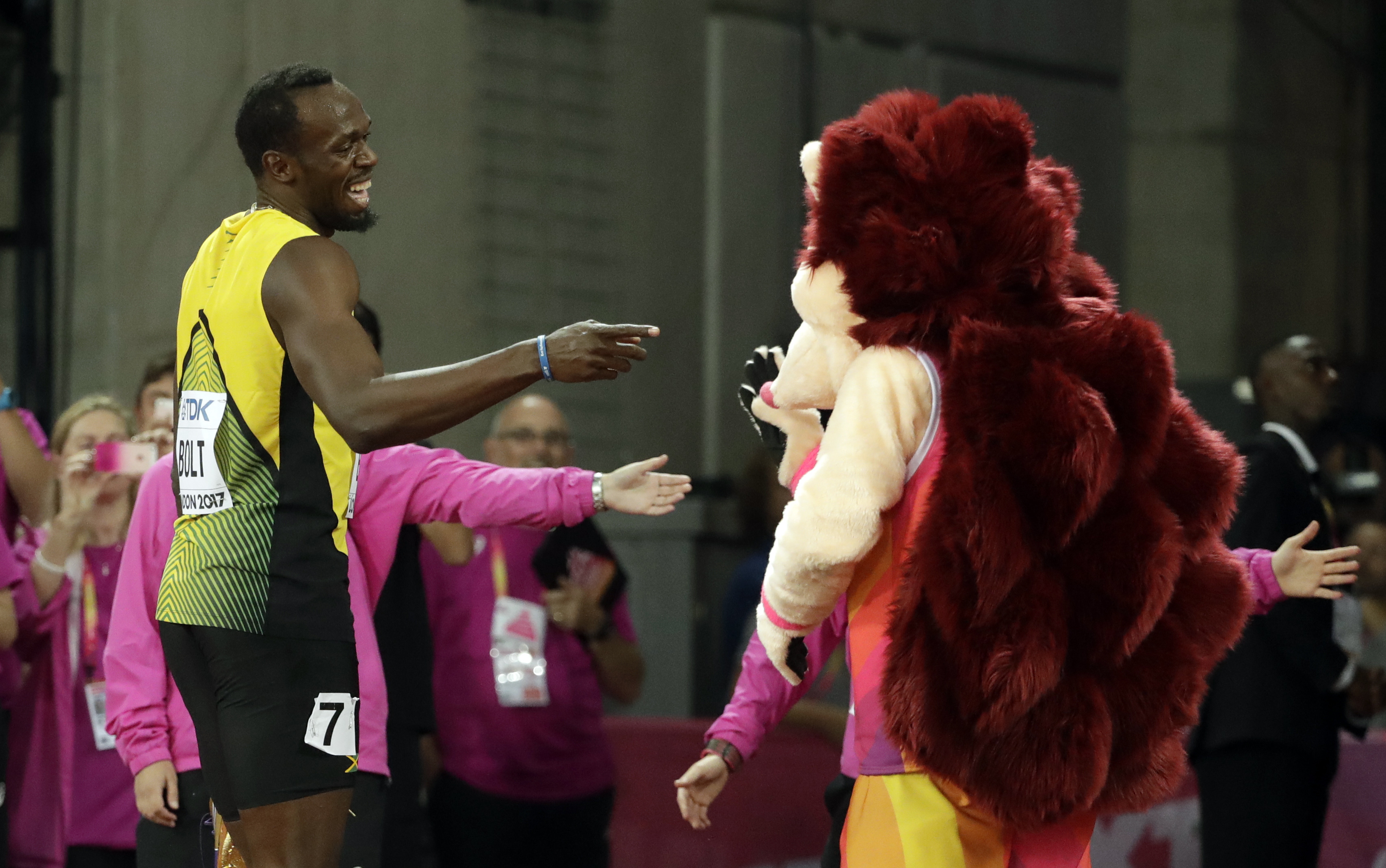 Jamaica's Usain Bolt jokes with mascot Hero the Hedgehog after his men's 100m heat during the World Athletics Championships in London Friday, Aug. 4, 2017. (AP Photo/Matthias Schrader)