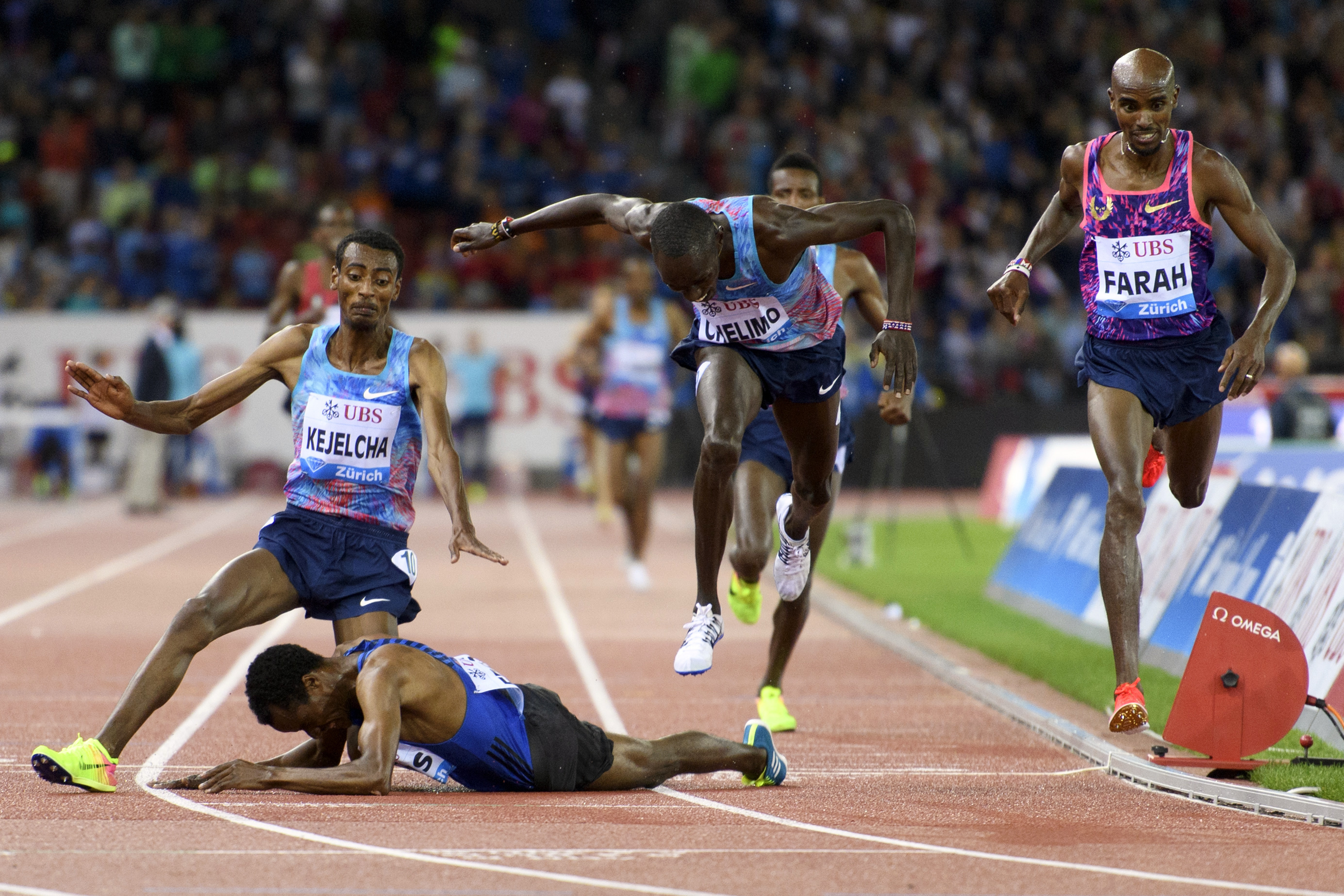 Mo Farah of Britain, right, crosses the finish line to win the Men's 5000m followed by second placed Paul Chelimo of United States, center right, and the falling Muktar Edris of Ethiopia, on the ground, during the Weltklasse IAAF Diamond League internatio
