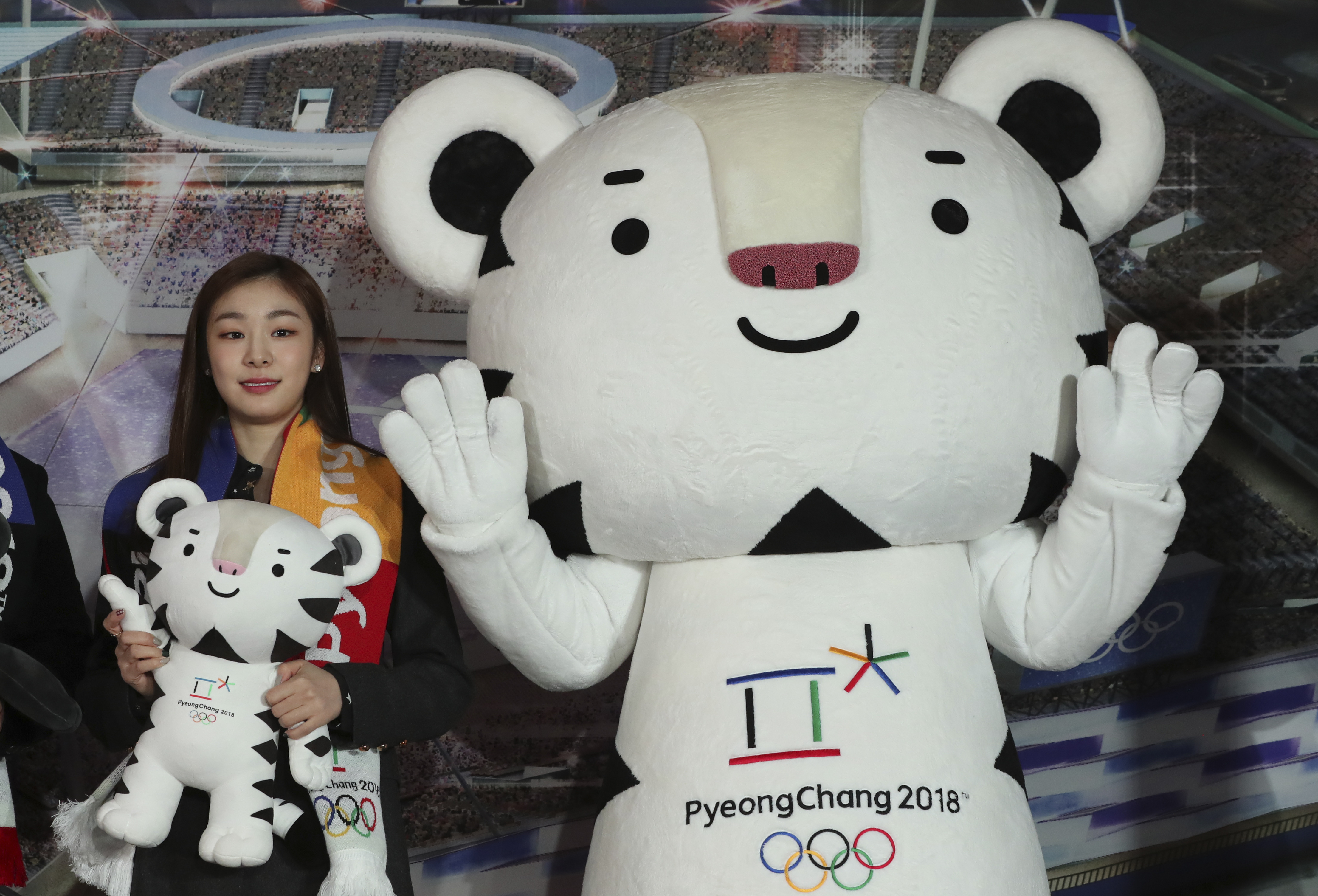 """FILE - In this Feb. 9, 2017, file photo, figure skating Olympics gold medalist Yuna Kim, an honorary ambassador for the 2018 Winter Olympics, poses with an official mascot of the 2018 Pyeongchang Olympic Winter Games, white tiger """"Soohorang,"""" at Gangneung"""
