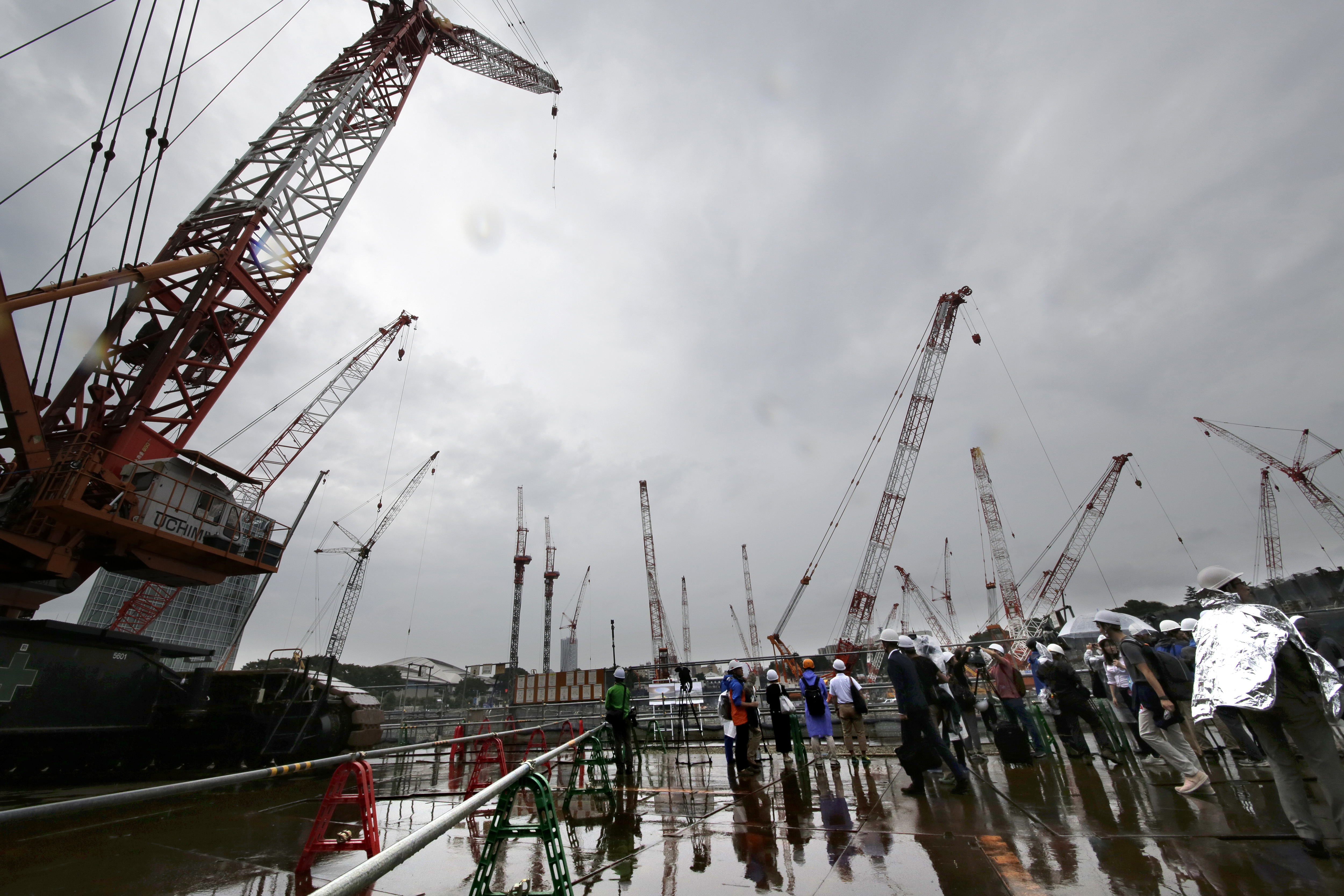 Members of the media review the construction of the new national stadium in Tokyo, Tuesday, Sept. 12, 2017. Tokyo's main Olympic stadium is starting to take shape as structures of what will become spectator stands are being installed after 10 months of un