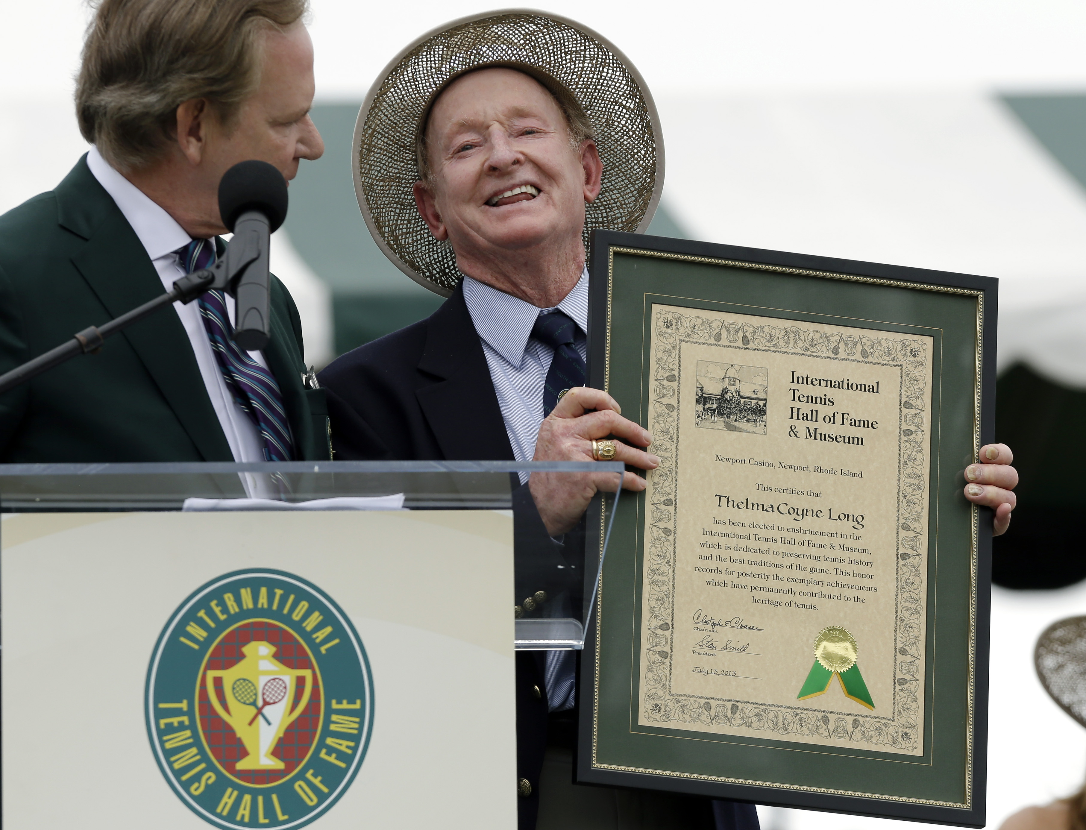 Tennis Hall of Famer Rod Laver, of Australia, accepts the enshrinement certificate for master player Thelma Coyne Long, 94, of Australia, who could not be there in person for her induction into the International Tennis Hall of Fame in Newport, R.I. Saturd