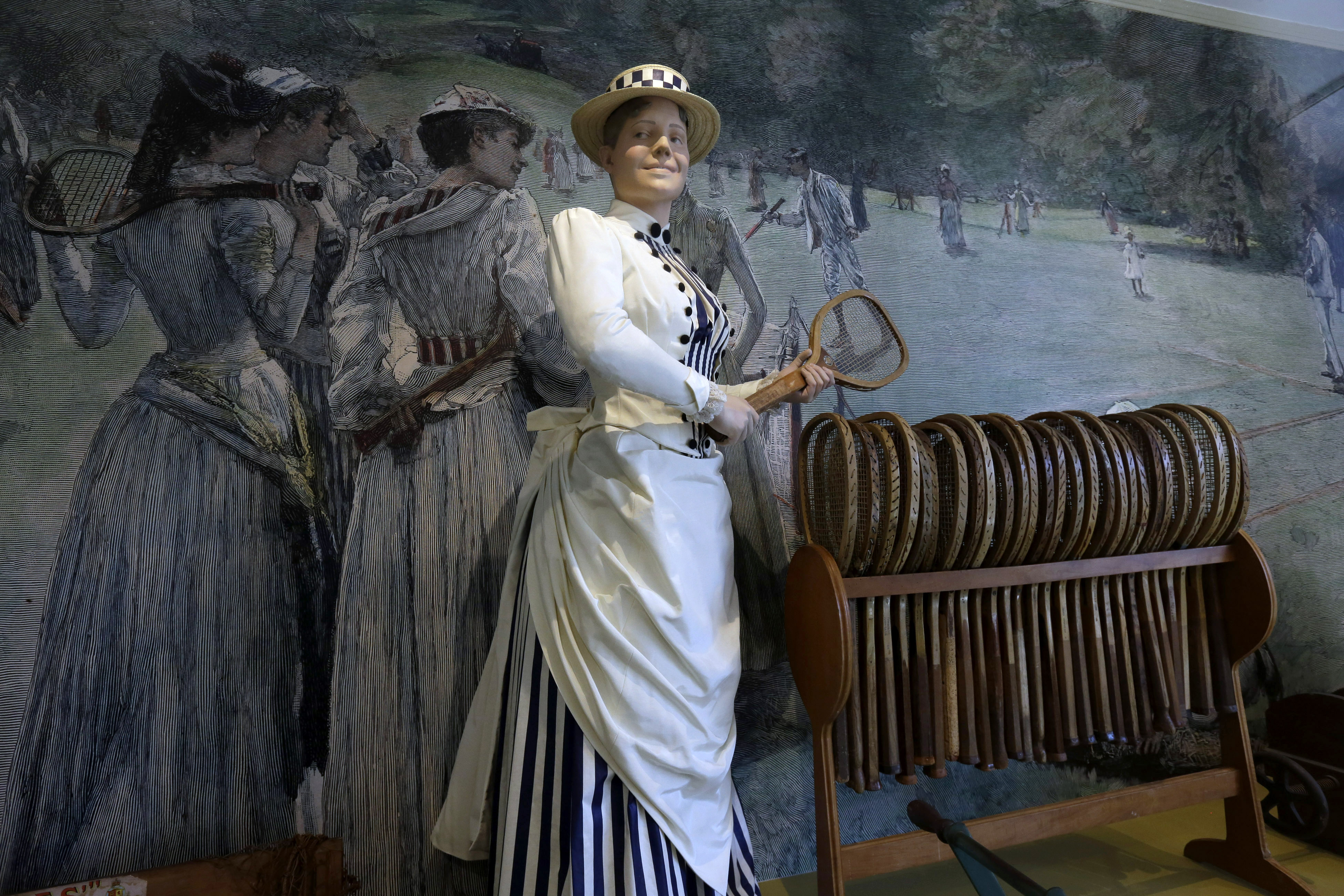 In this Monday, May 11, 2015 photo, a mannequin, dressed in early twentieth fashion is placed next to a tennis racquet stand of the same period, in a display case at the International Tennis Hall of Fame, in Newport, R.I.  The International Tennis Hall of