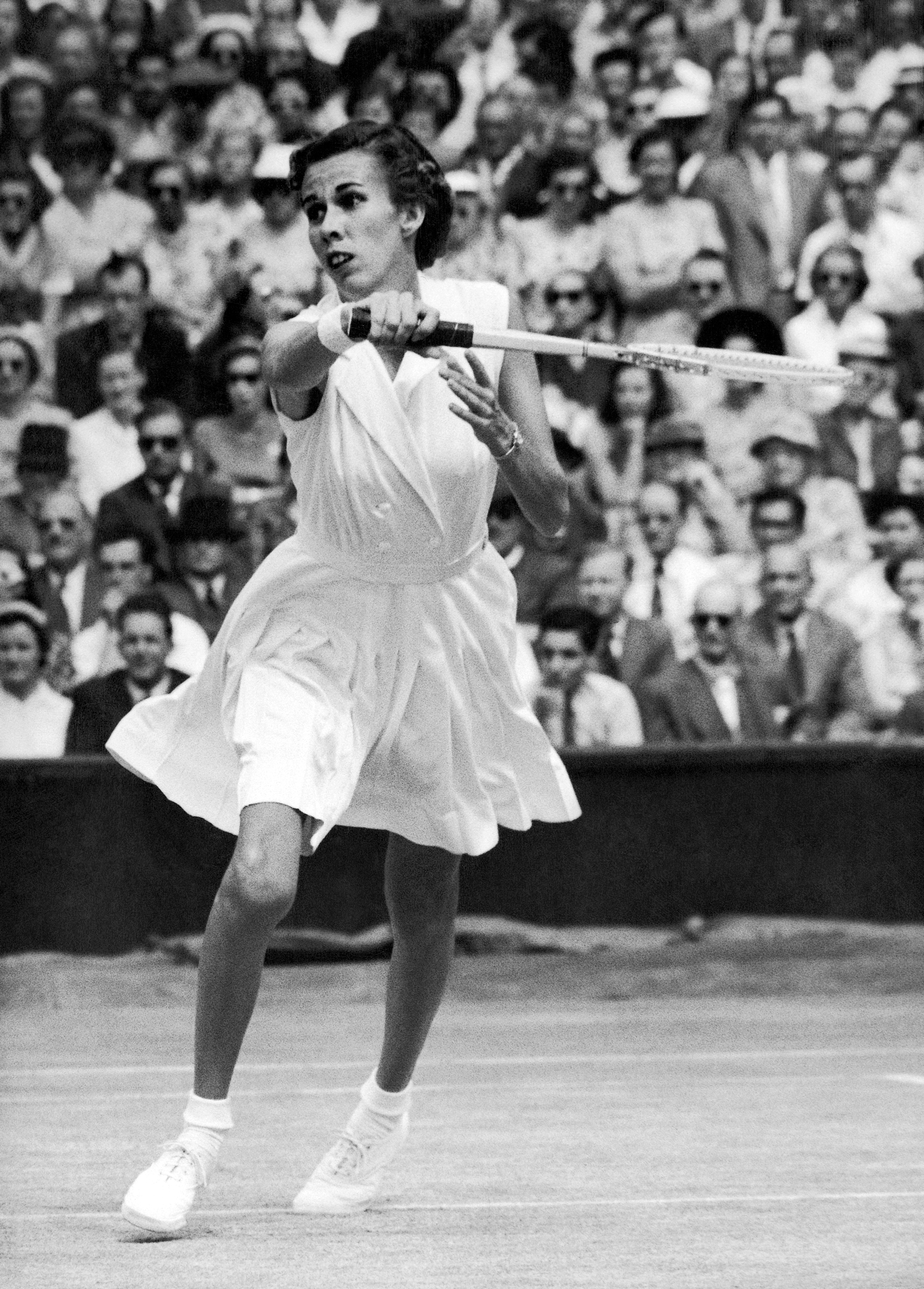 FILE - In this July 2, 1953, file photo, Doris Hart hits a return against Dorothy Head Knode in the semifinals match of All-England lawn tennis Championships at Wimbledon, London, England. Hart, who won each Grand Slam tournament at least once, and once w