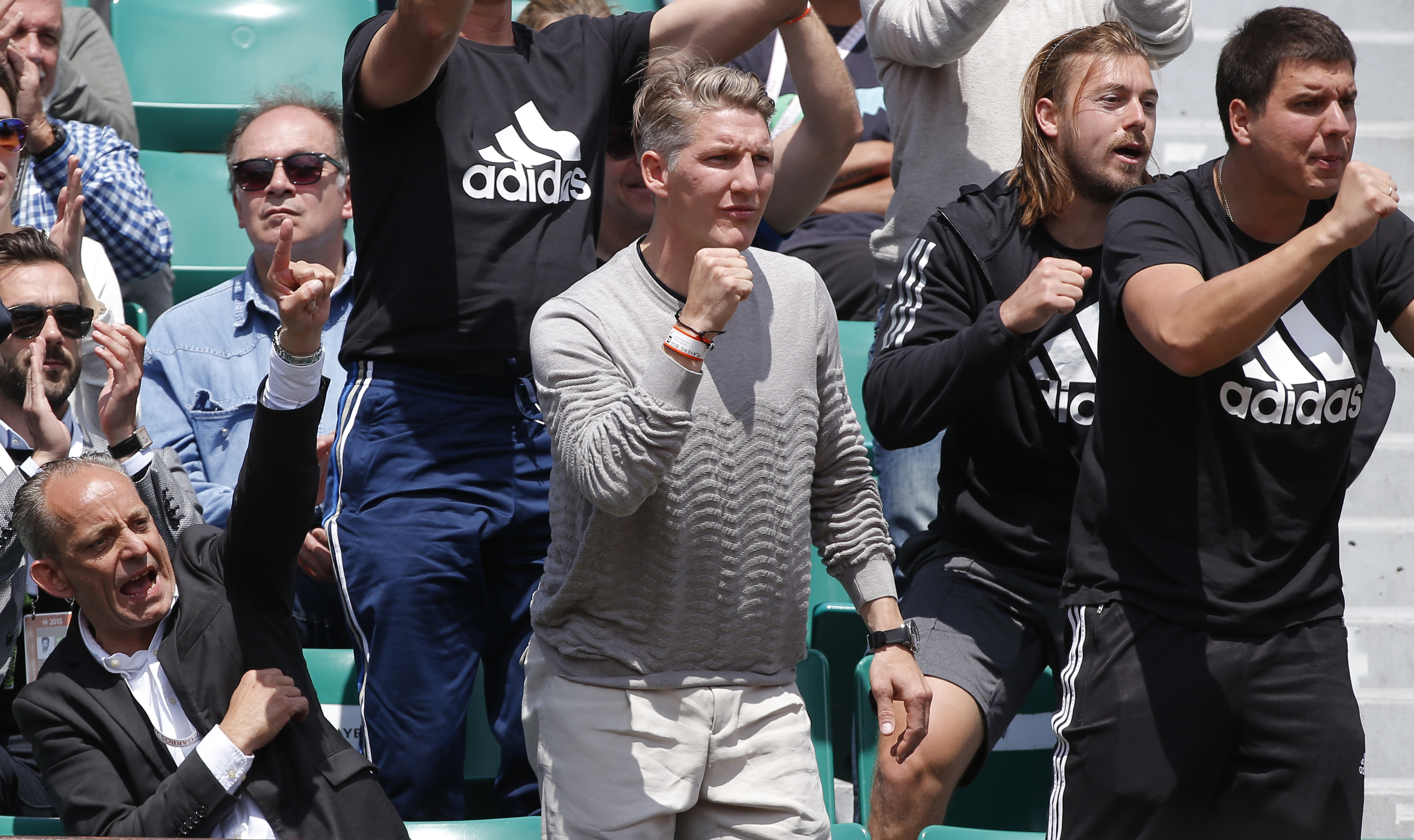 Bayern soccer player Germany's Bastian Schweinsteiger, standing at center,  clenches his fist as Serbia's Ana Ivanovic plays Ukraine's Elina Svitolina during their quarterfinal match of the French Open tennis tournament at the Roland Garros stadium, Tuesd