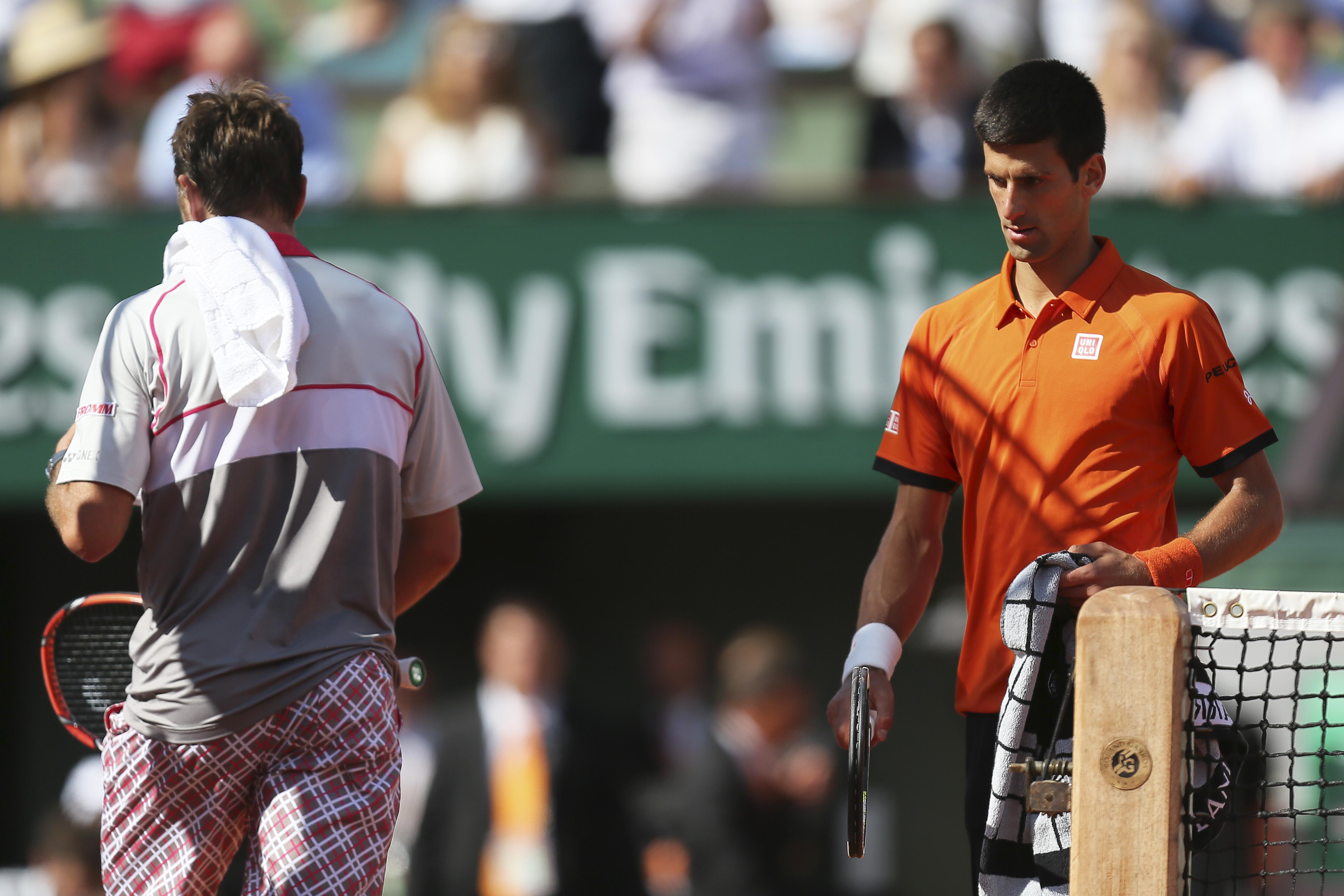 Serbia's Novak Djokovic, right, passes Switzerland's Stan Wawrinka in the men's final of the French Open tennis tournament at the Roland Garros stadium, in Paris, France, Sunday, June 7, 2015. (AP Photo/David Vincent)