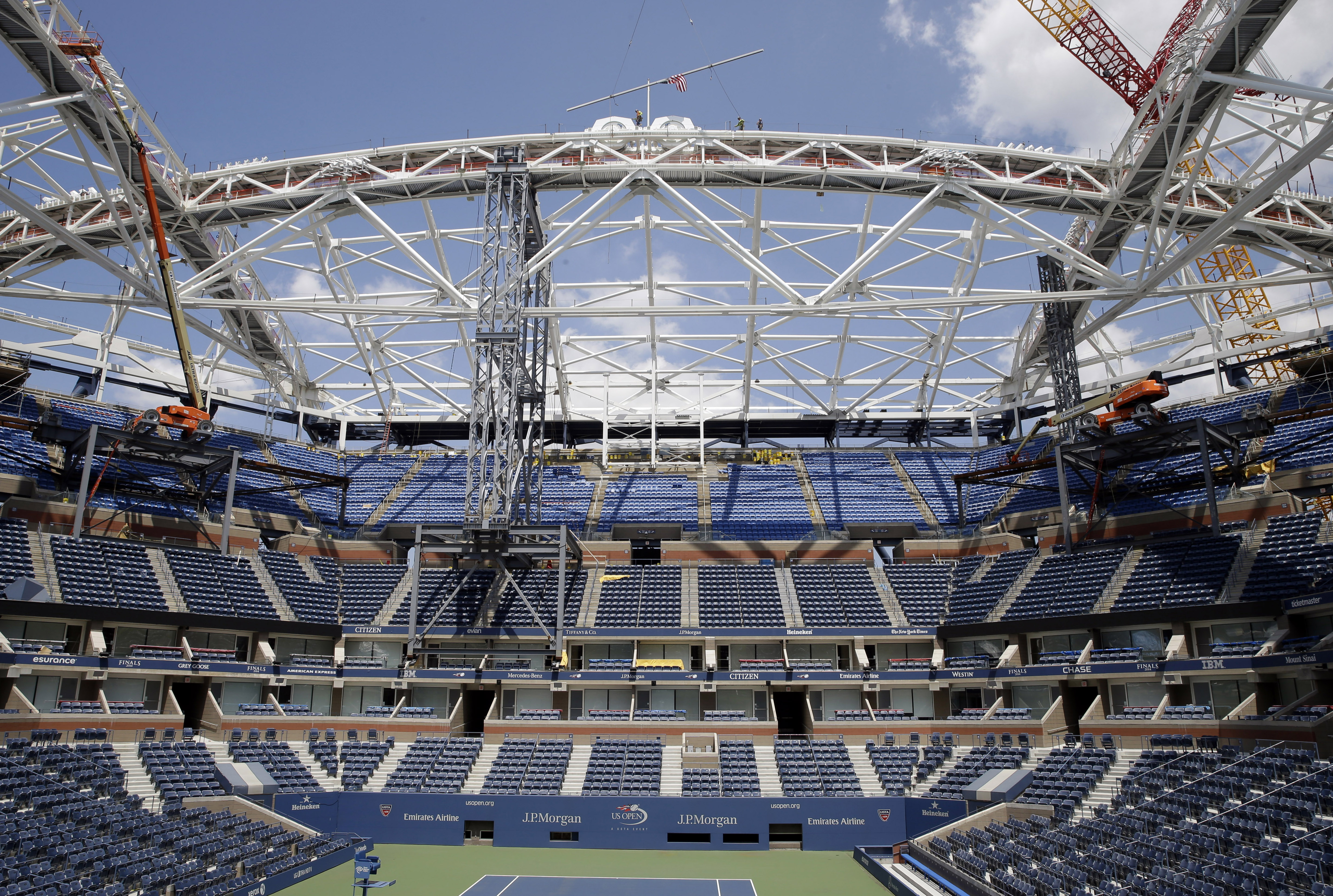 Construction workers place the final piece of steel in the superstructure that will support the retractable roof over the Arthur Ashe Stadium, Wednesday, June 10, 2015, in New York. While Wimbledon and the Australian Open already put retractable roofs ove
