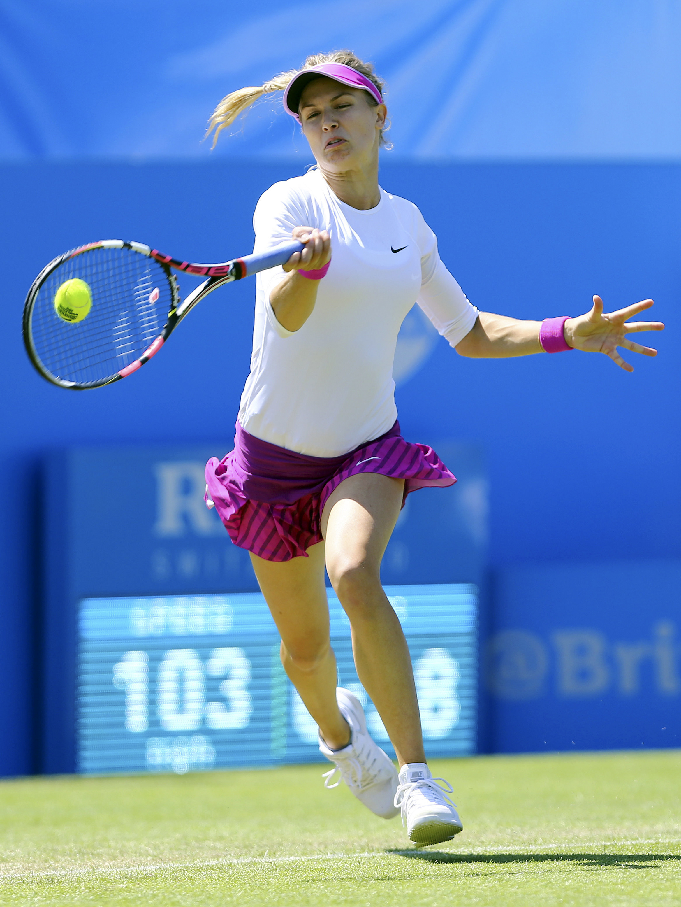 Canada's Eugenie Bouchard returns the ball to Switzerland's Belinda Bencic during day five of the women's international tennis tournament at Devonshire Park, Eastbourne, England, Wednesday June 24, 2015. (Gareth Fuller/PA via AP) UNITED KINGDOM OUT  NO SA