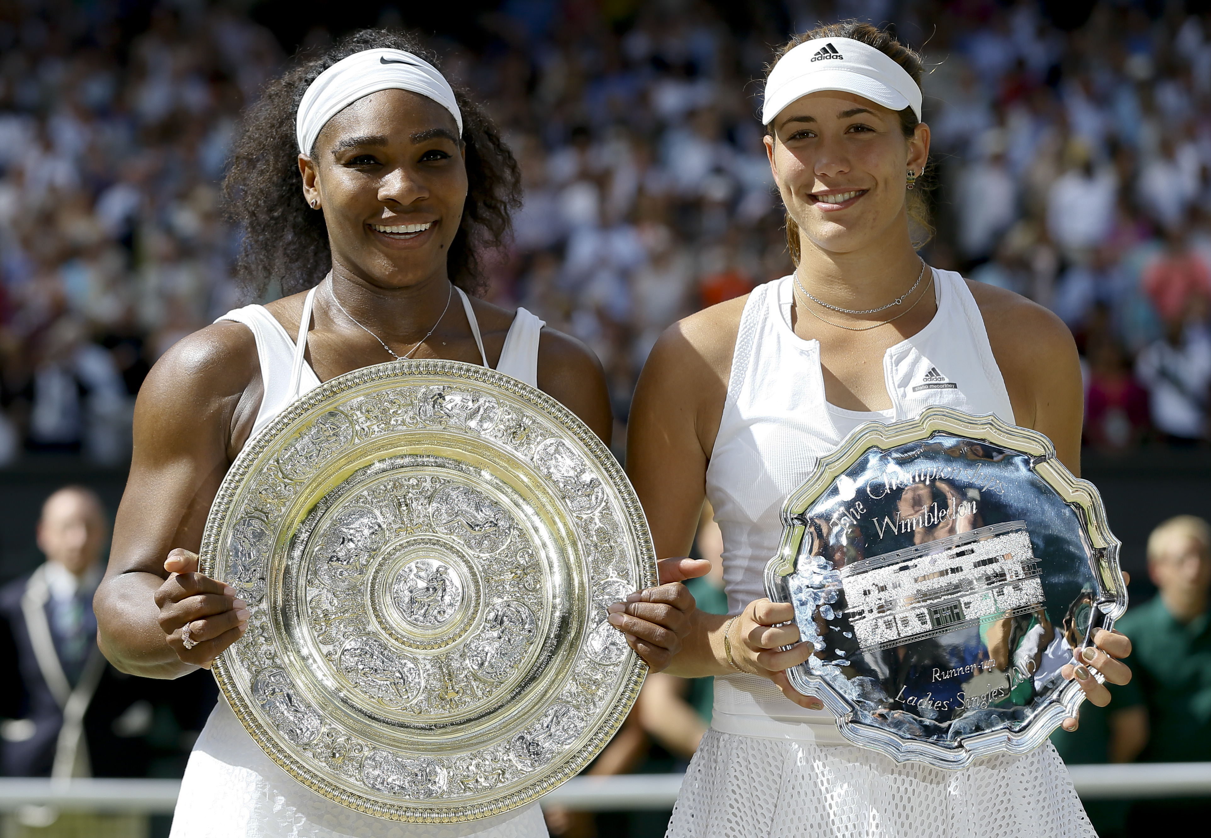 Serena Williams of the United States, left and  Garbine Muguruza of Spain hold up their trophies after the women's singles final against at the All England Lawn Tennis Championships in Wimbledon, London, Saturday July 11, 2015. Williams won 6-4, 6-4. (AP