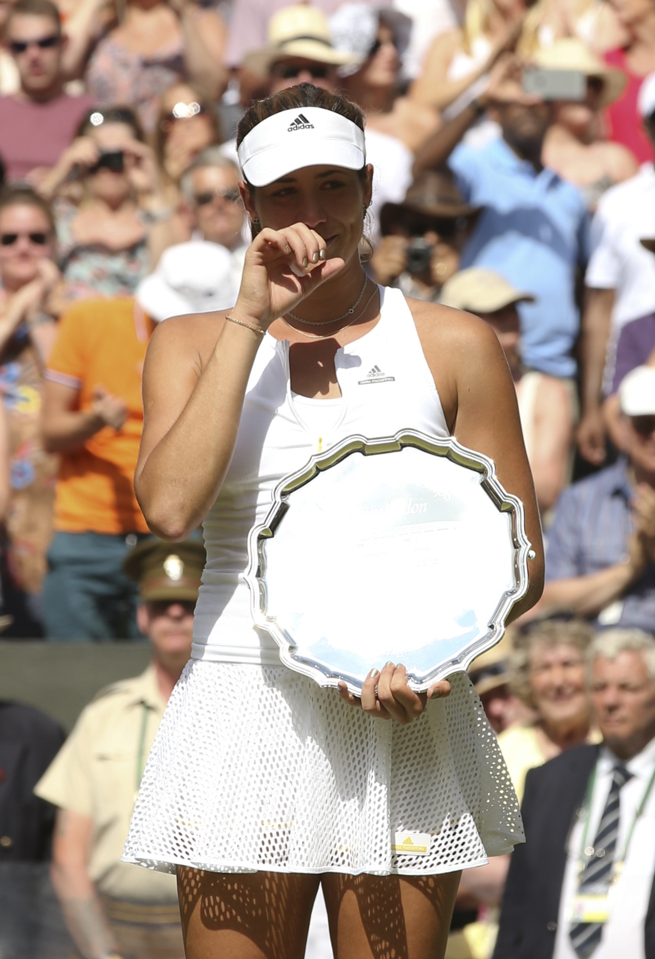 Garbine Muguruza of Spain cries as she holds the runners up trophy during the trophy ceremony after losing to Serena Williams of the United States, at the All England Lawn Tennis Championships in Wimbledon, London, Saturday July 11, 2015. (Sean Dempsey/Po