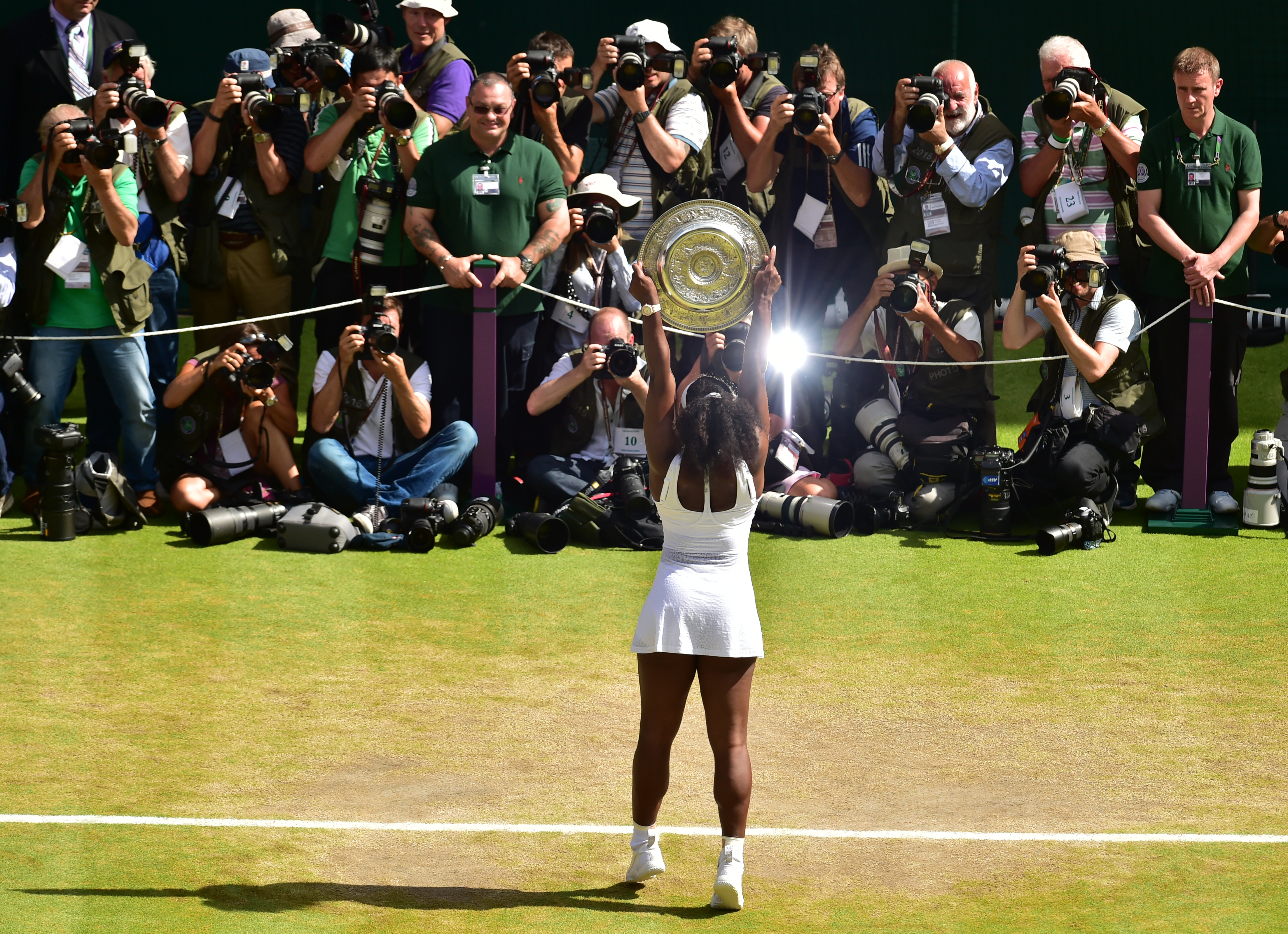 Serena Williams of the United States holds up the trophy toward the media after winning the women's singles final against Garbine Muguruza of Spain at the All England Lawn Tennis Championships in Wimbledon, London, Saturday July 11, 2015. (Dominic Lipinsk