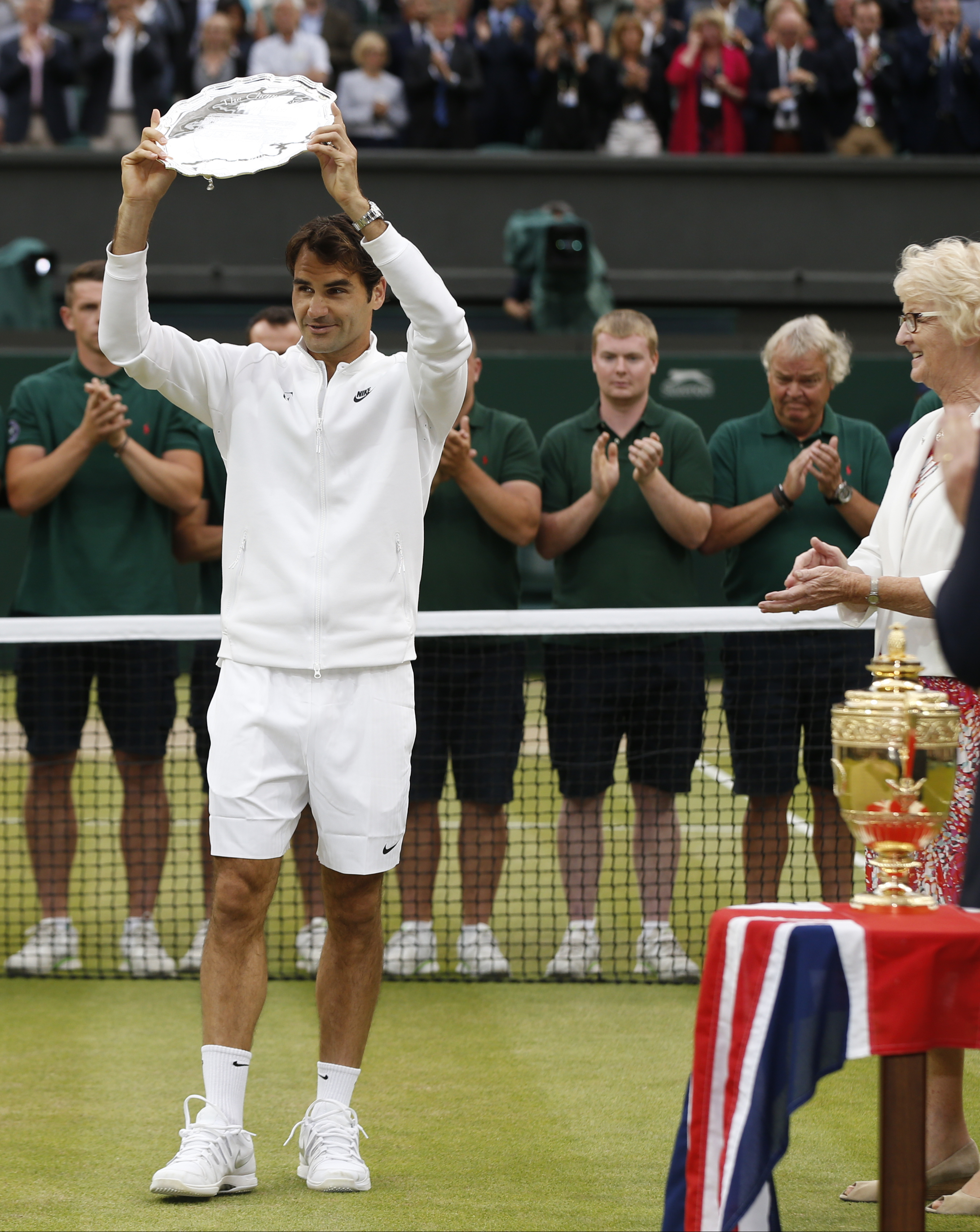 Roger Federer of Switzerland holds up the runner up trophy up after being defeated by Novak Djokovic of Serbia in the men's singles final at the All England Lawn Tennis Championships in Wimbledon, London, Sunday July 12, 2015. Djokovic won the match 7-6,