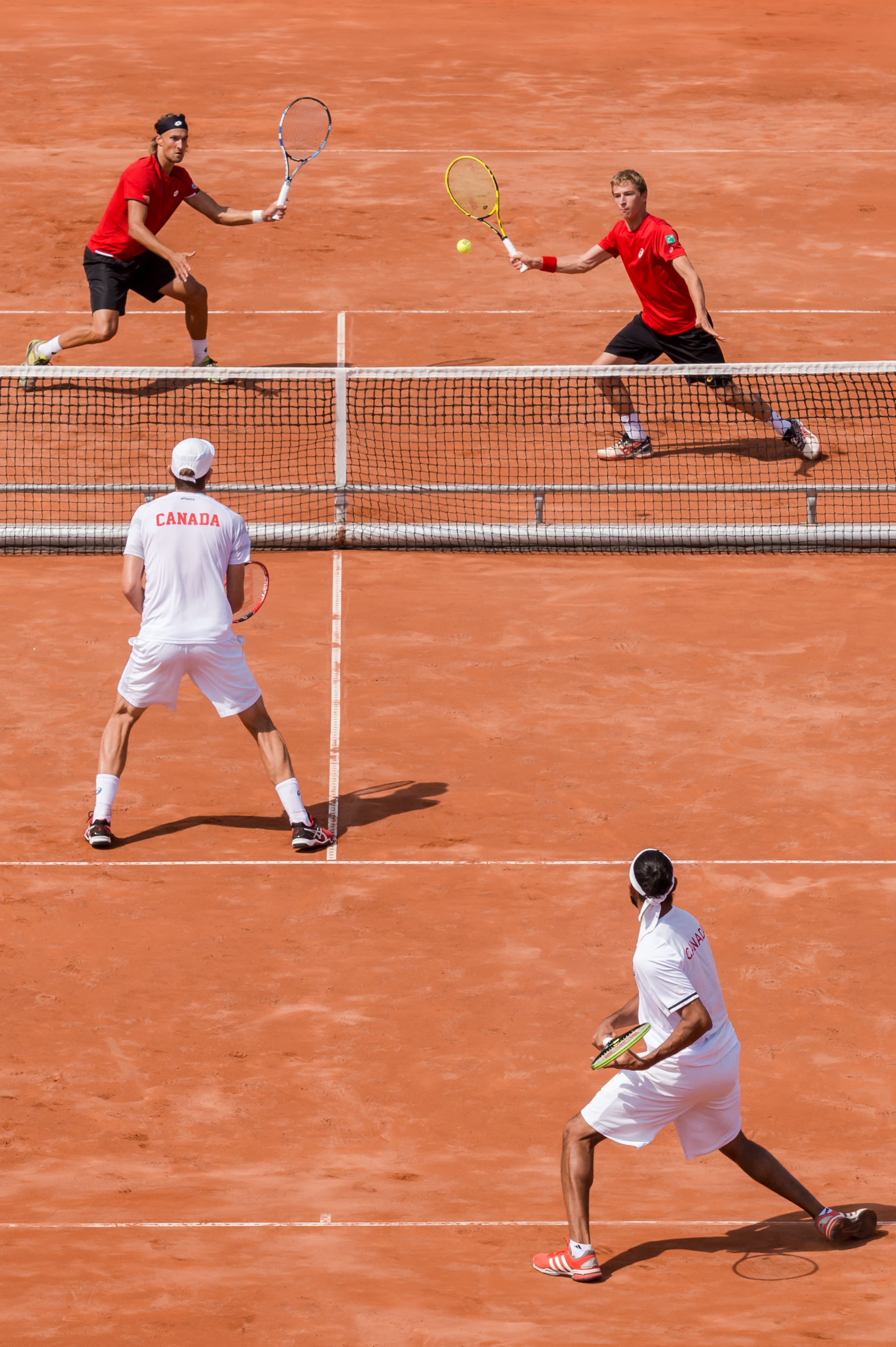 Belgium's Ruben Bemelmans, top left, and Kimmer Coppejans, top right, return the ball to Canada's Daniel Nestor, center, and Adil Shamasdin during the Davis Cup World Group quarterfinal match between Belgium and Canada, in Middelkerke, Belgium, on Saturda