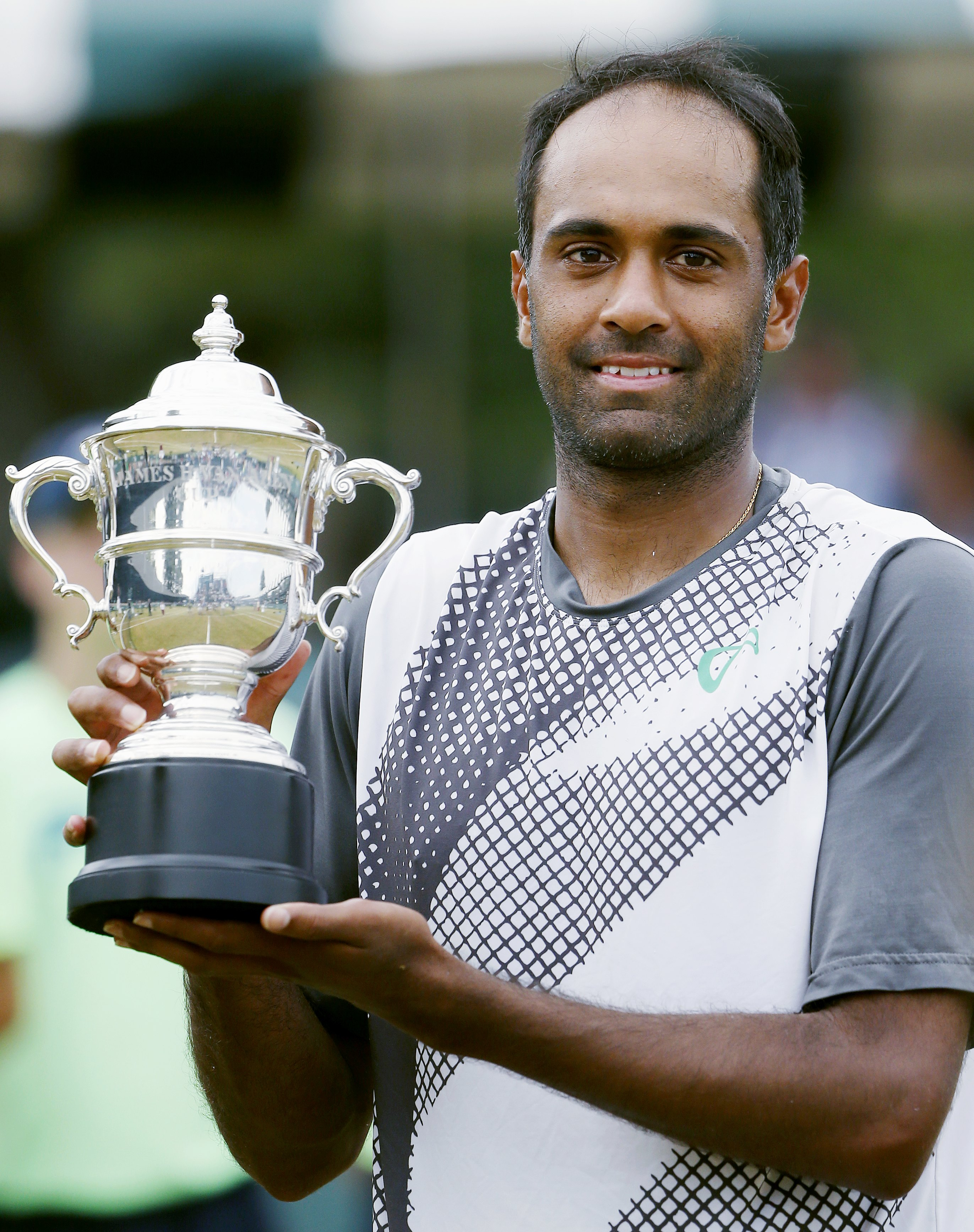 Rajeev Ram holds the trophy after defeating Ivo Karlovic, of Croatia, in the Tennis Hall of Fame Championship final in Newport, R.I., Sunday, July 19, 2015. (AP Photo/Michael Dwyer)