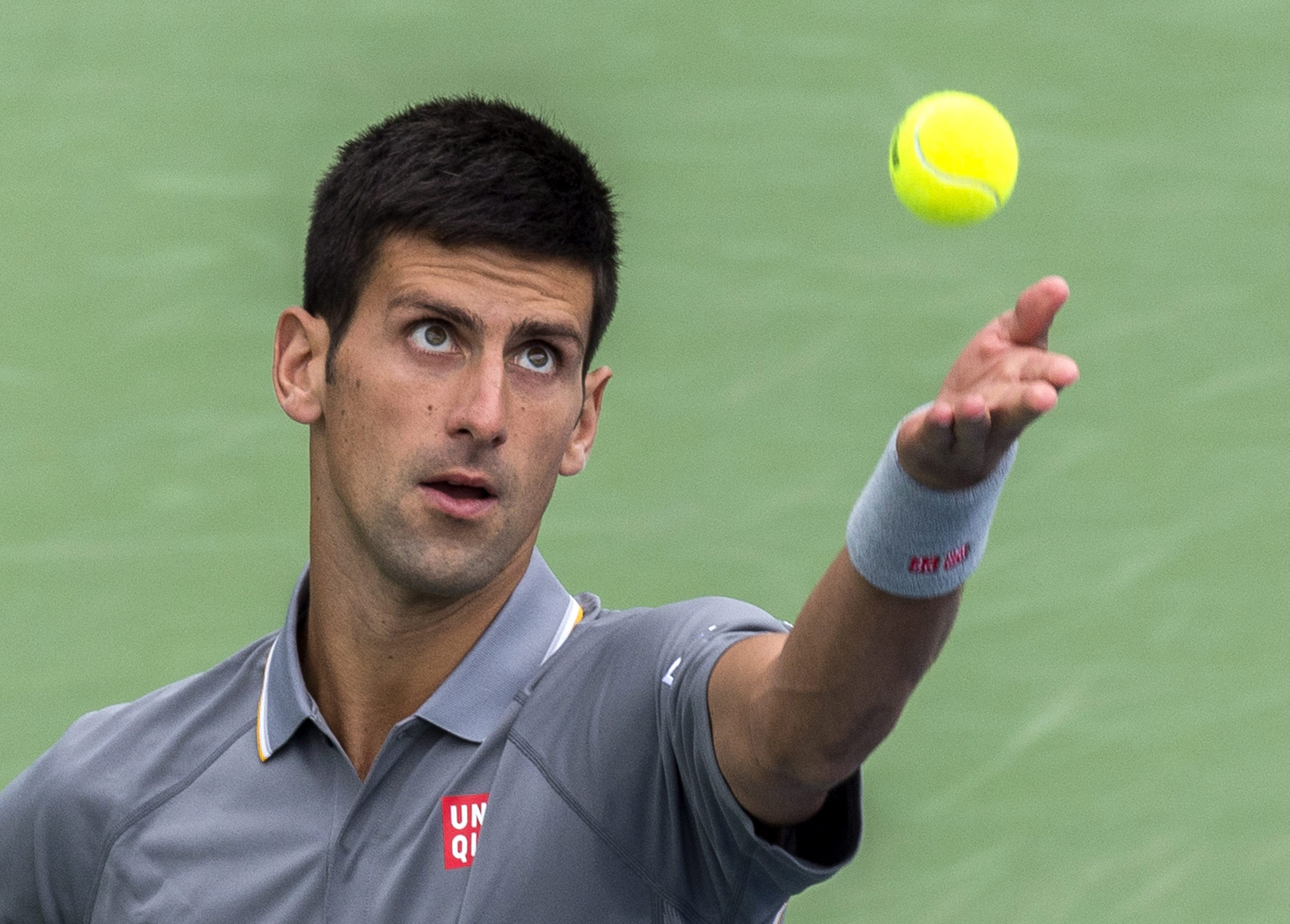 Novak Djokovic, of Serbia, tosses the ball to serve to Jack Sock, of the United States, during the Rogers Cup men's tennis tournament in Montreal, Thursday, Aug. 13, 2015. (Paul Chiasson/The Canadian Press via AP) MANDATORY CREDIT